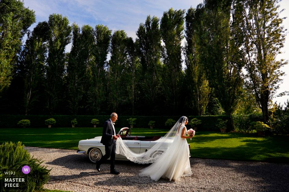 Convento dell'Annunciata, Medole, Mantova | La mariée passe devant la voiture et vers l'église.