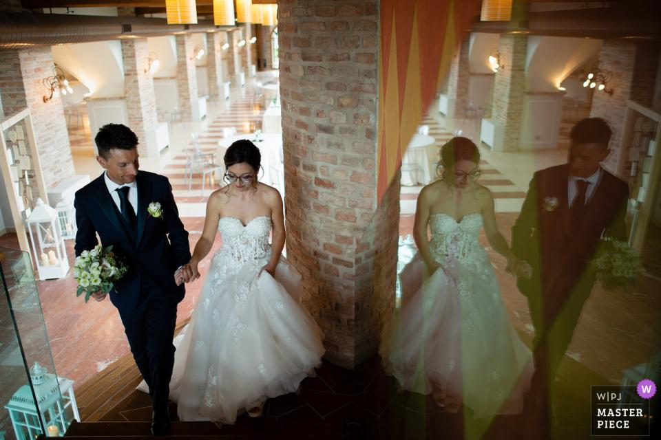 La Corte Berghemina, Pagazzano Hochzeitsfoto der Braut und des Bräutigams, die die Treppe zum Beginn der Hochzeitsfeier hinaufgehen