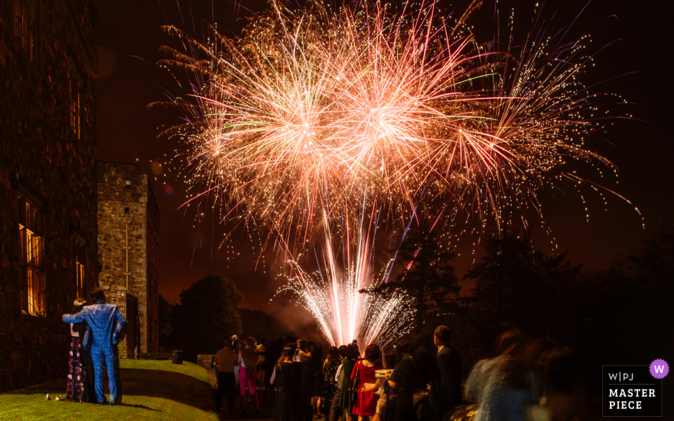 wedding reportage photography from the Waterford Castle, Ireland of fireworks with Bride and Groom looking on