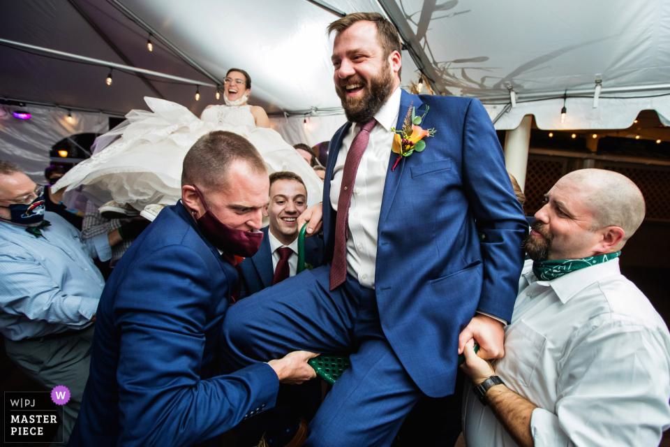 Desmond Hotel Malvern, Pennsylvanie photographie de mariage montrant le marié soulevé en l'air pour l'hora avec la mariée en arrière-plan