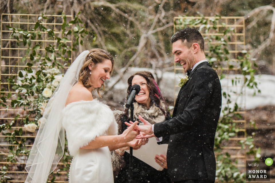 Tahoe City, CA bride and groom laugh and smile while eyeing the groom's ring during a snowy, outdoor ceremony at Granlibakken Resort