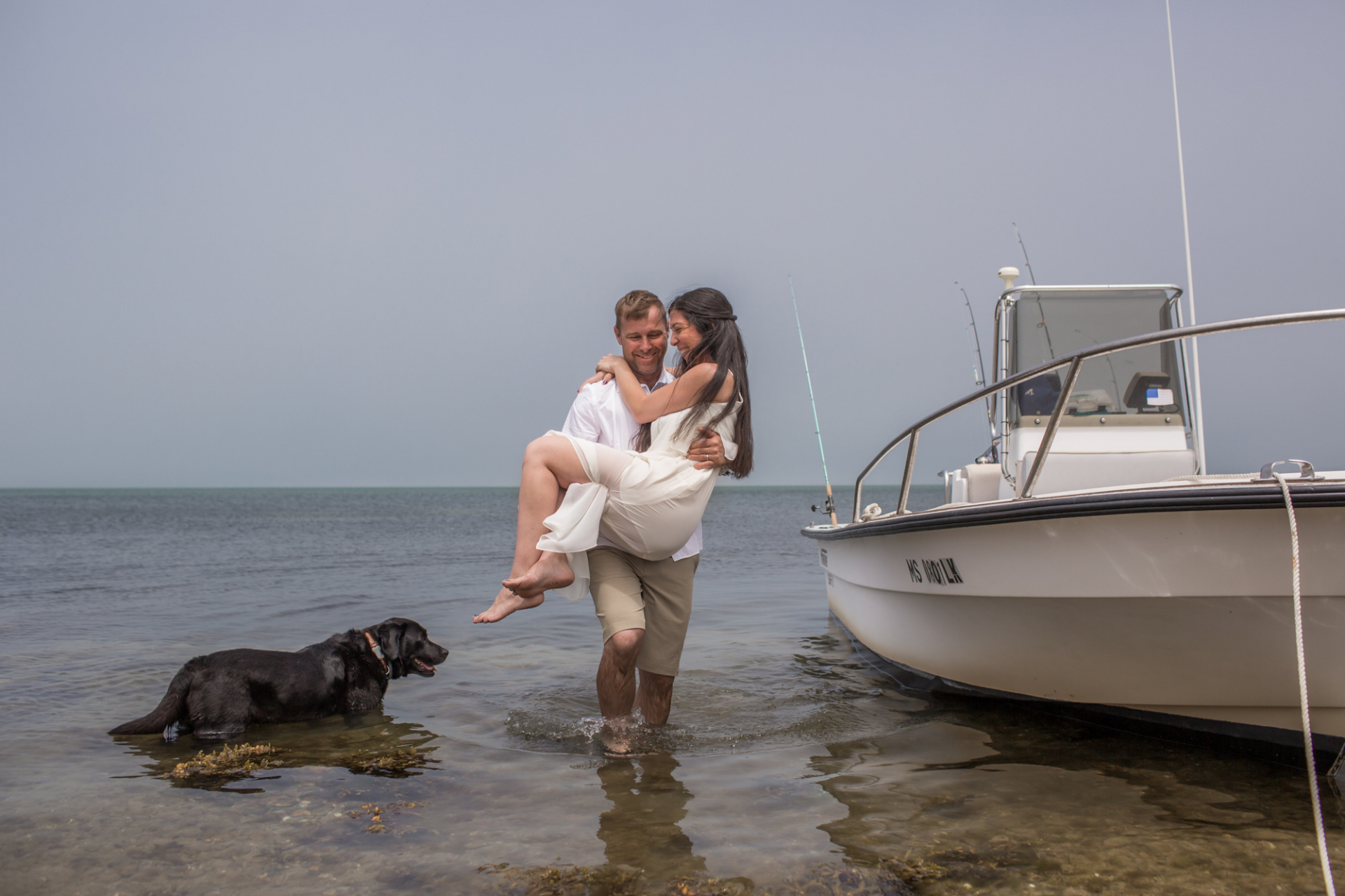 Groom carries new wife from the boat to the shore on an Island, MA