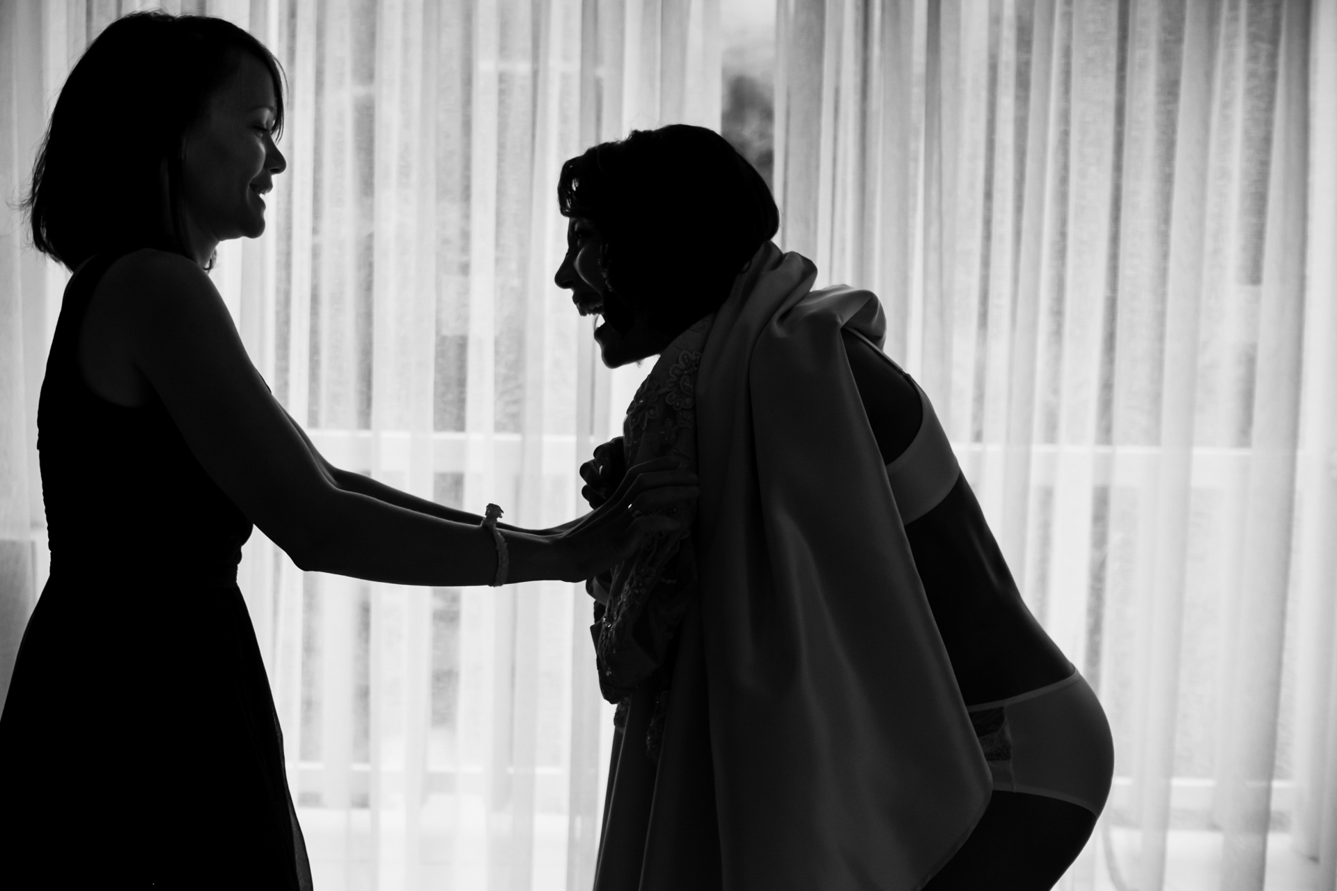 The bride and her sister (all the way from the US), shares a comical moment while trying to get her dress on before her South Africa Elopement Wedding