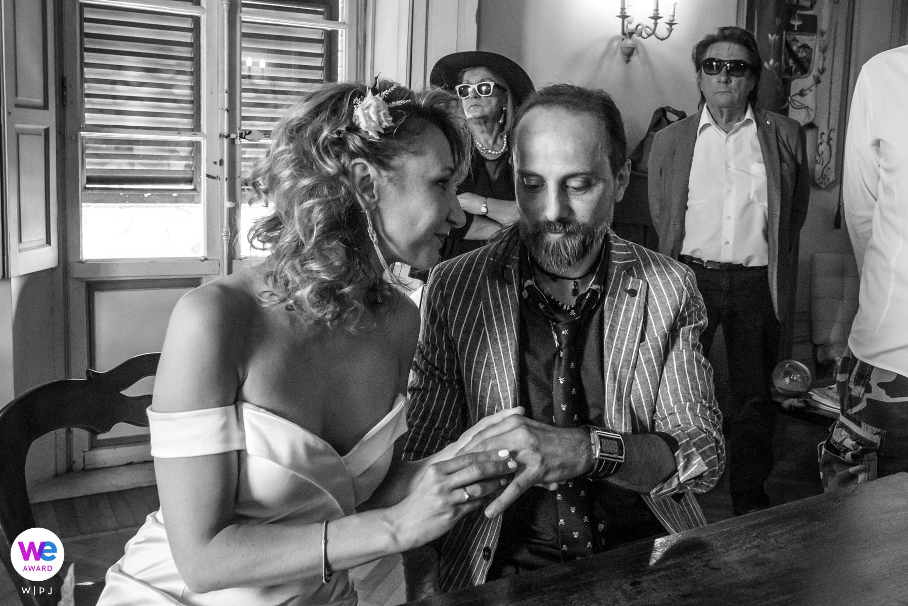 Parma, Italien Elopement Image Gallery - Die Braut versucht, ihre Gefühle zurückzuhalten und beobachtet das Gesicht des Bräutigams, während er den Ring auflegt.