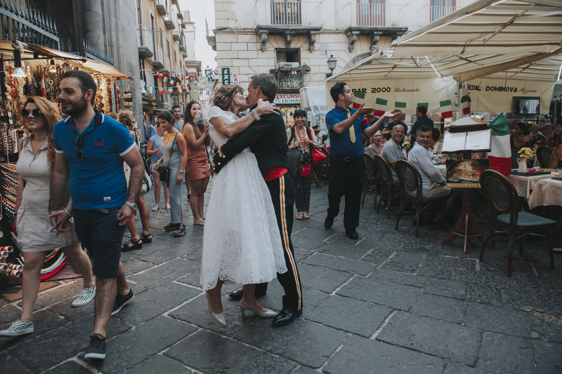 """Once hundreds of people saw the bride and groom they started a warm applause and the waiter of the restaurant incite people sitted to have a toast with them. At the """"Kiss"""" request ...well, that is the photo at Sorrento, Amalfi Coast, Italy"""