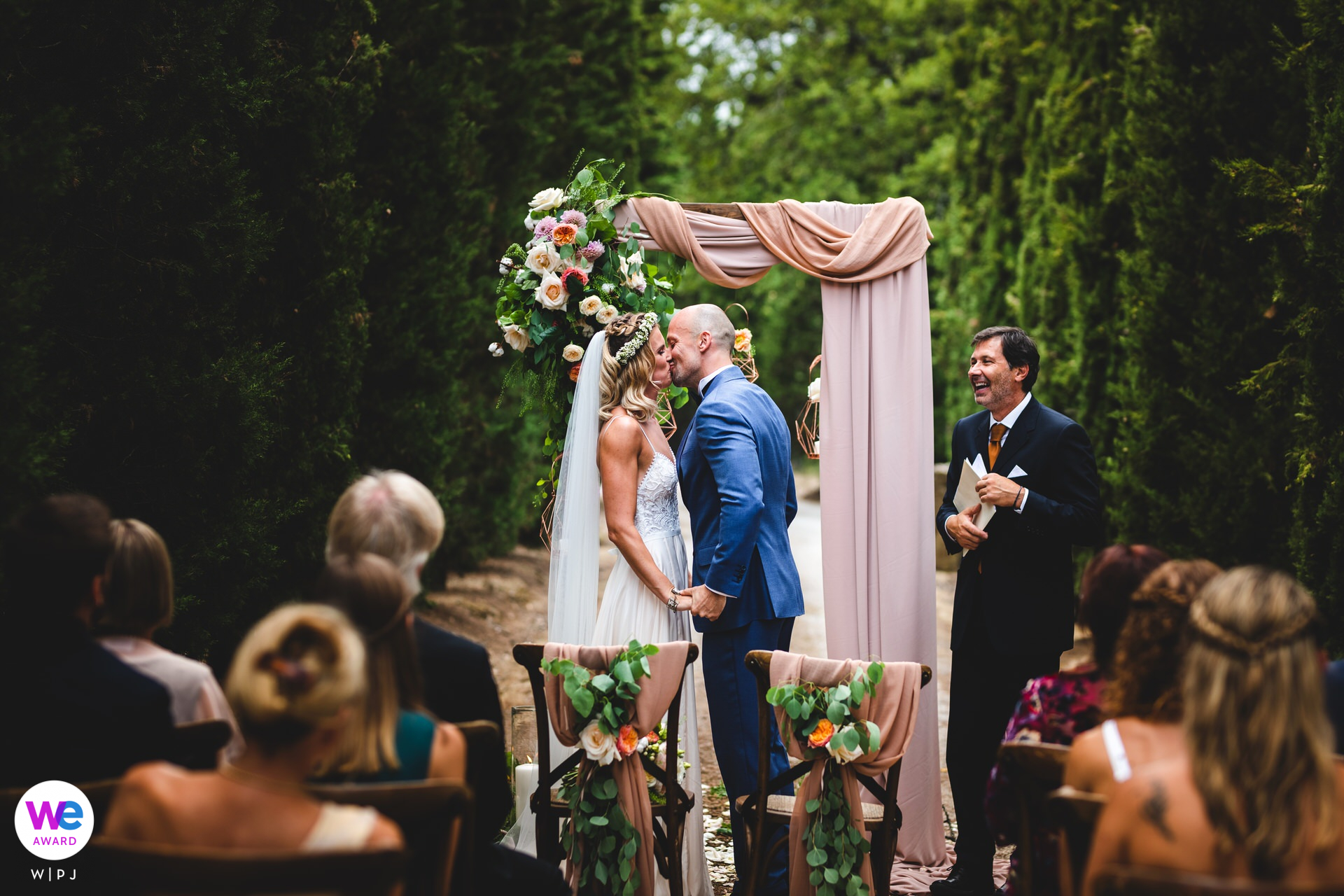 Tuscany Elopement Picture | The bride and groom chose to have their small, private ceremony among tall, green shrubbery, affording them the intimacy to share that classic kiss after saying yes!