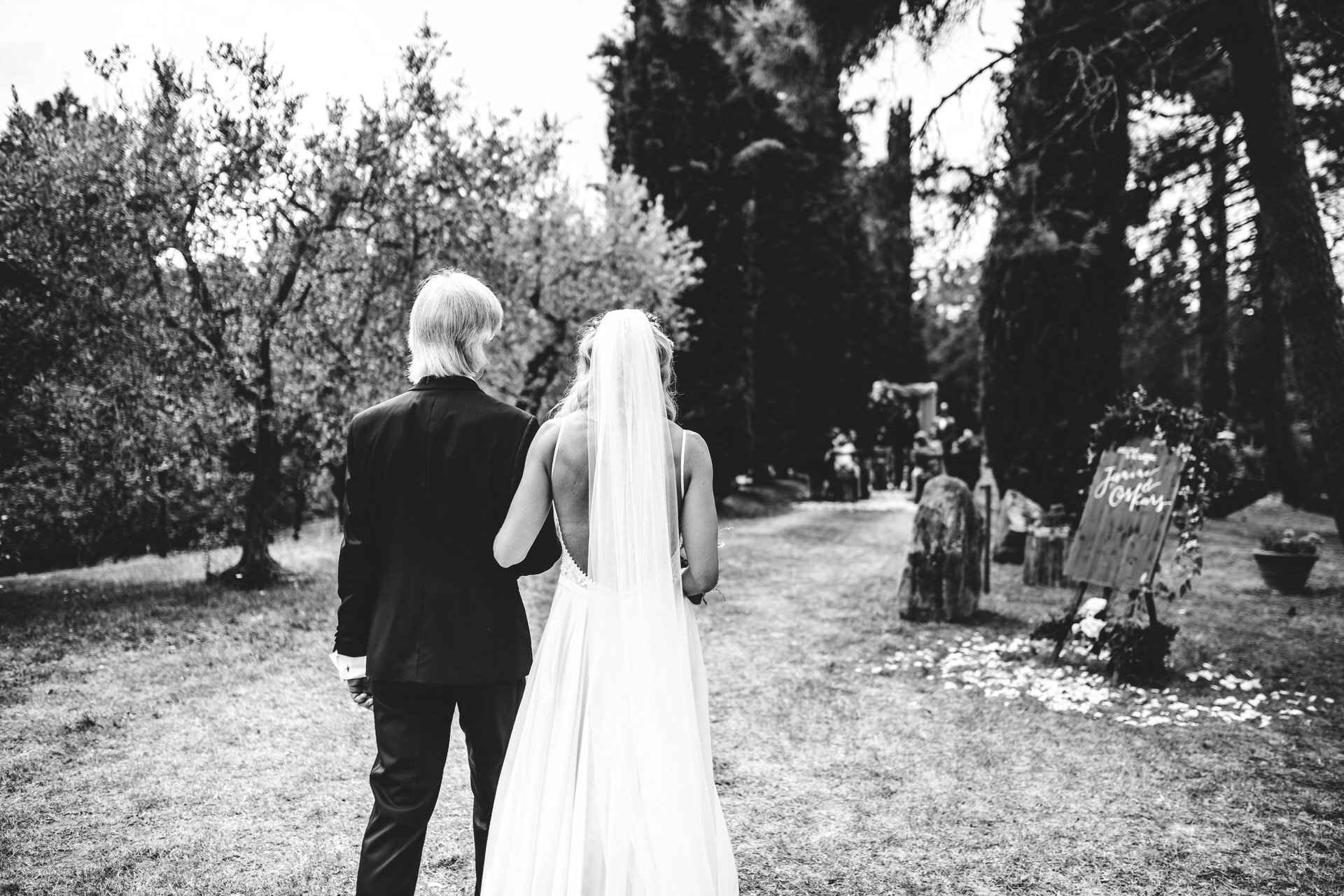 The bride and her father arrive at the symbolic ceremony in the garden of villa at Villa Olimpia, Ambra, Tuscany