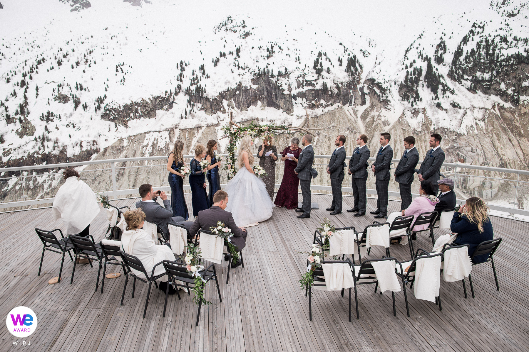 Chamonix, French Alps Elopement | All the guests sat on the outdoor deck during the elopement wedding in Chamonix, surrounded by breathtaking, snow-filled scenery.