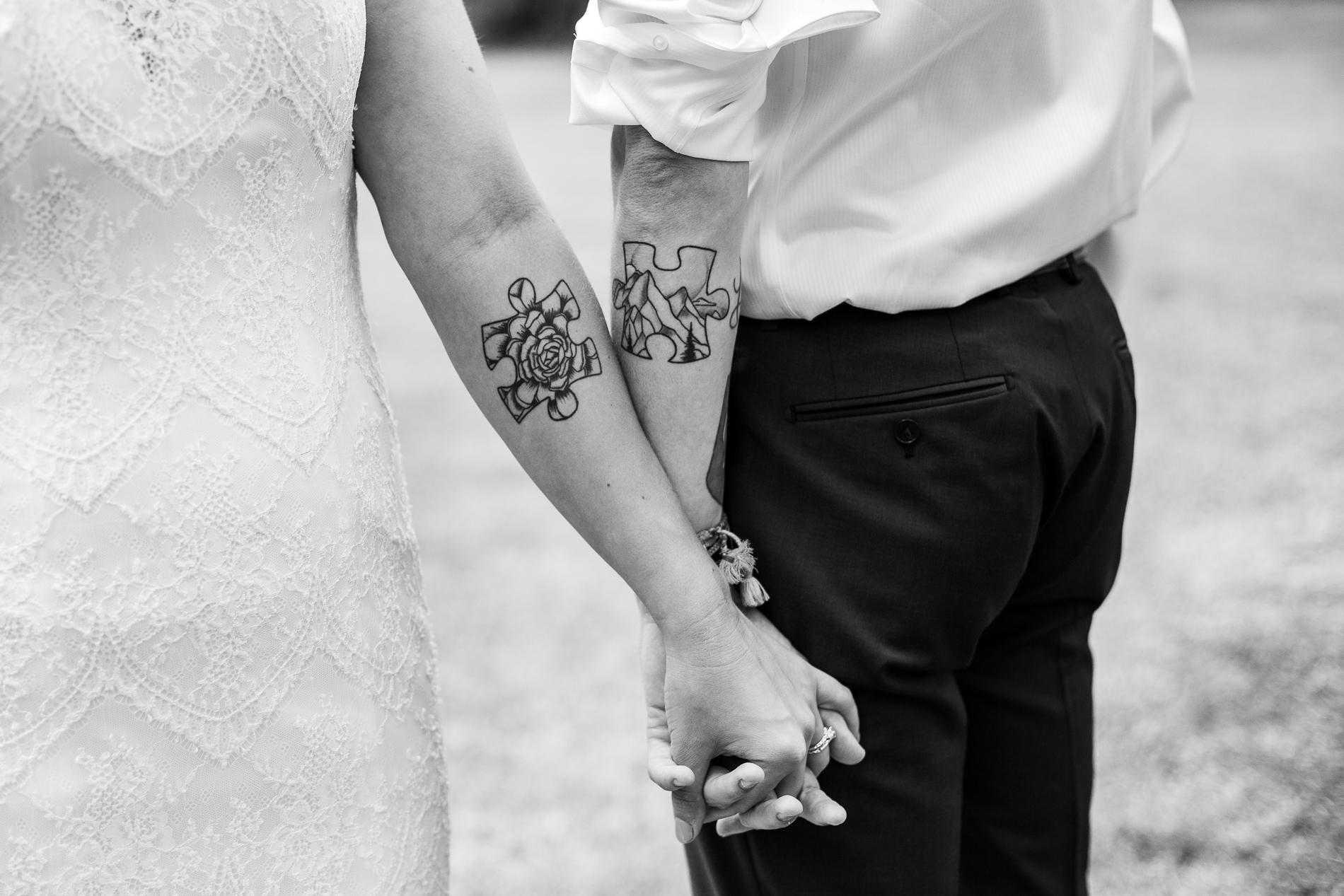Photo détaillée de tatouages de pièces de puzzle assorties alignées sur les bras du couple - Black Canyon Inn, Estes Park Elopement Picture