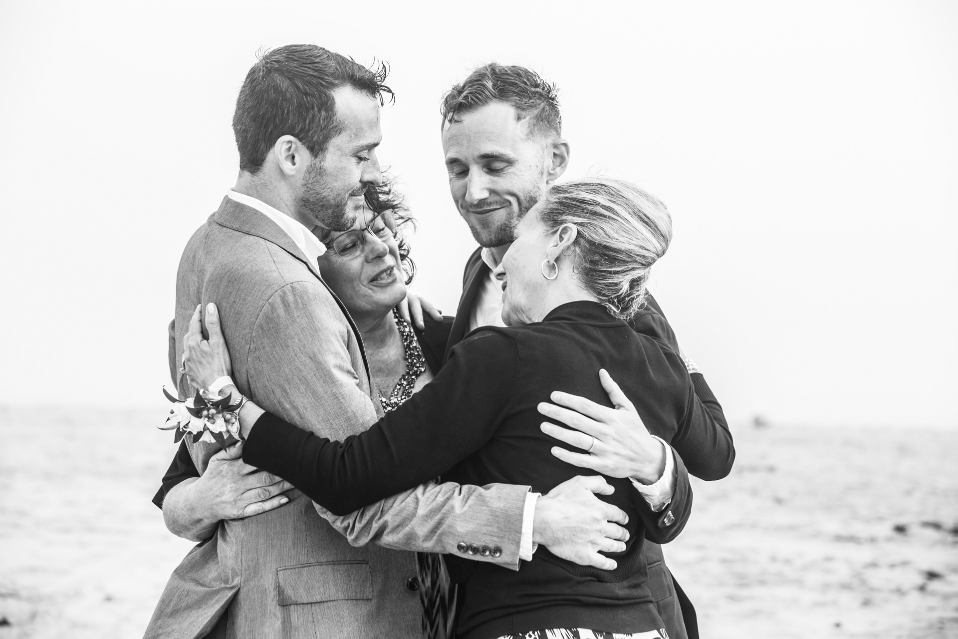 Image from a beach elopement ceremony at Nantucket Island, MA | Grooms share a dance and group hug with their moms after the ceremony.