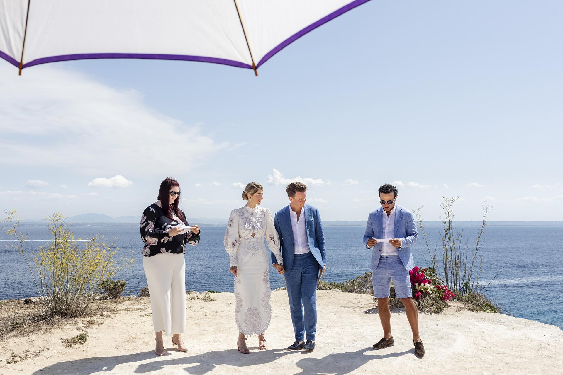 Elopement à Favignana Island, Sicile Photo | Le témoin du mariage lit ses recommandations aux époux.