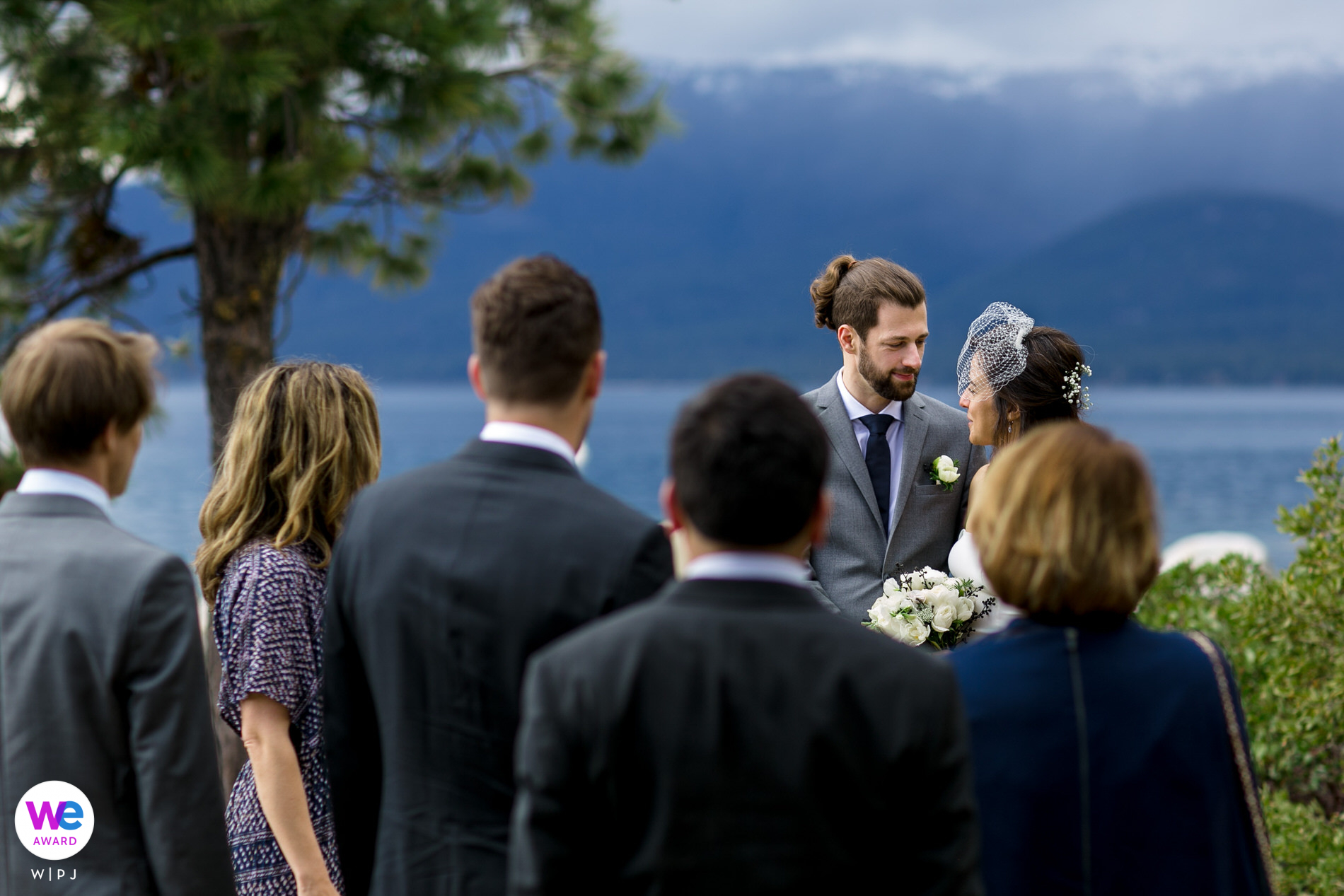Nevada State Park Elopement Images | The groom and bride look at one another during their small wedding ceremony. Lake Tahoe is in the background. The rain clouds are moving closer and the light on the lake is becoming more dramatic.