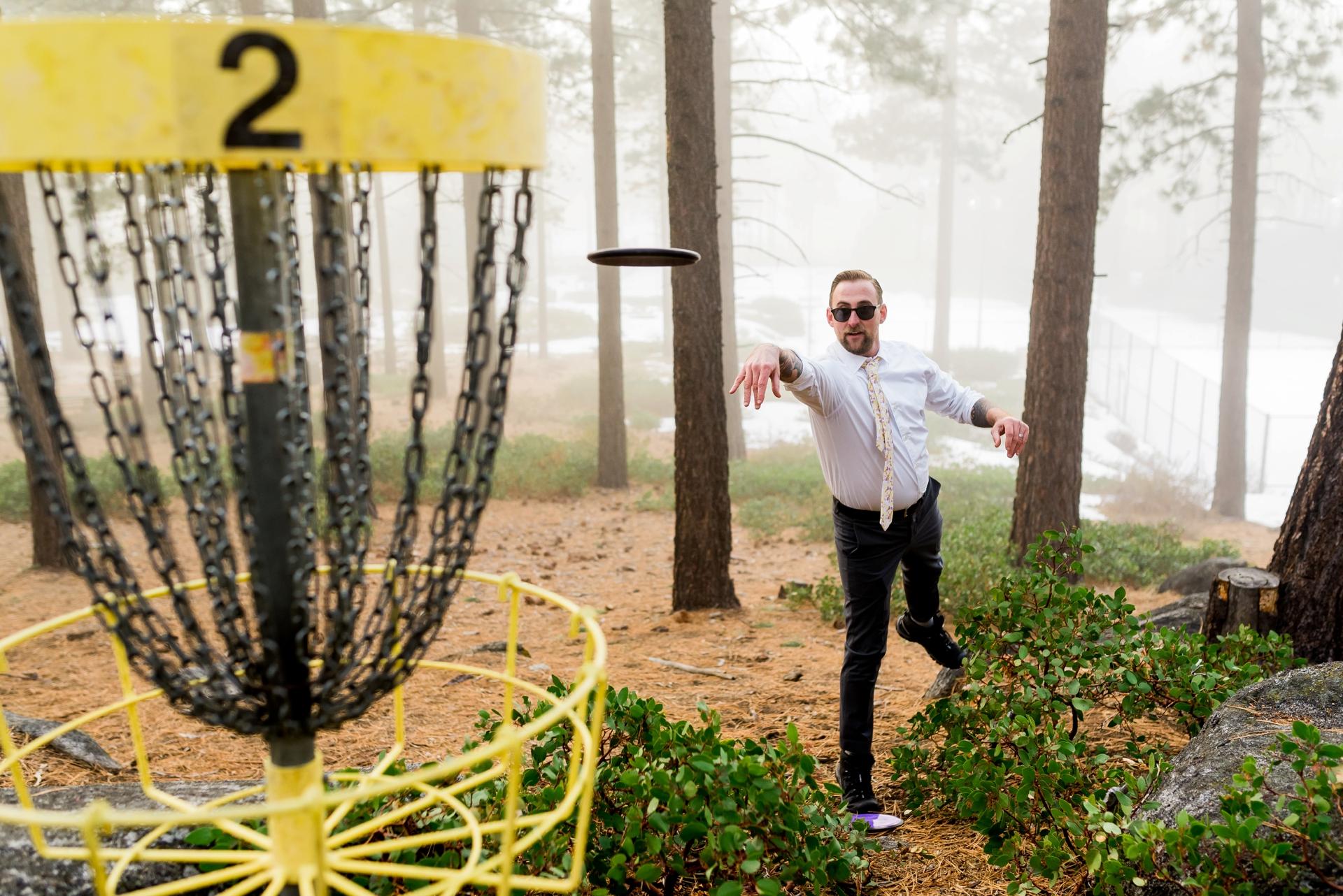 Nevada Elopement Photo - Le marié lance un golf à disque vers le panier.