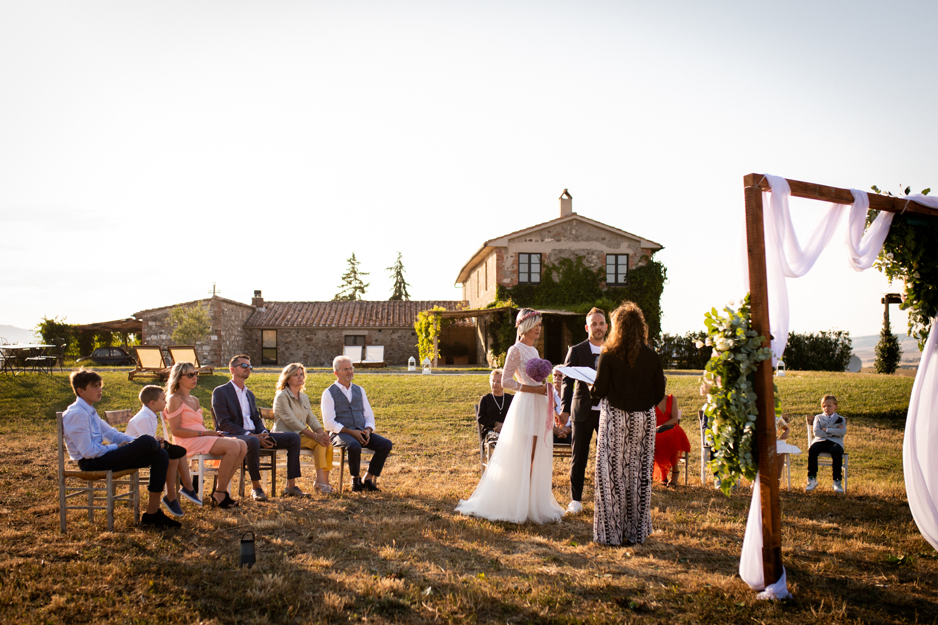 Tuscany Outdoor Elopement Ceremony Picture | The setting of the outdoor small wedding ceremony. The bride and groom with their relatives during the sunset in front of the celebrant and a wooden arc decorated with colored roses.
