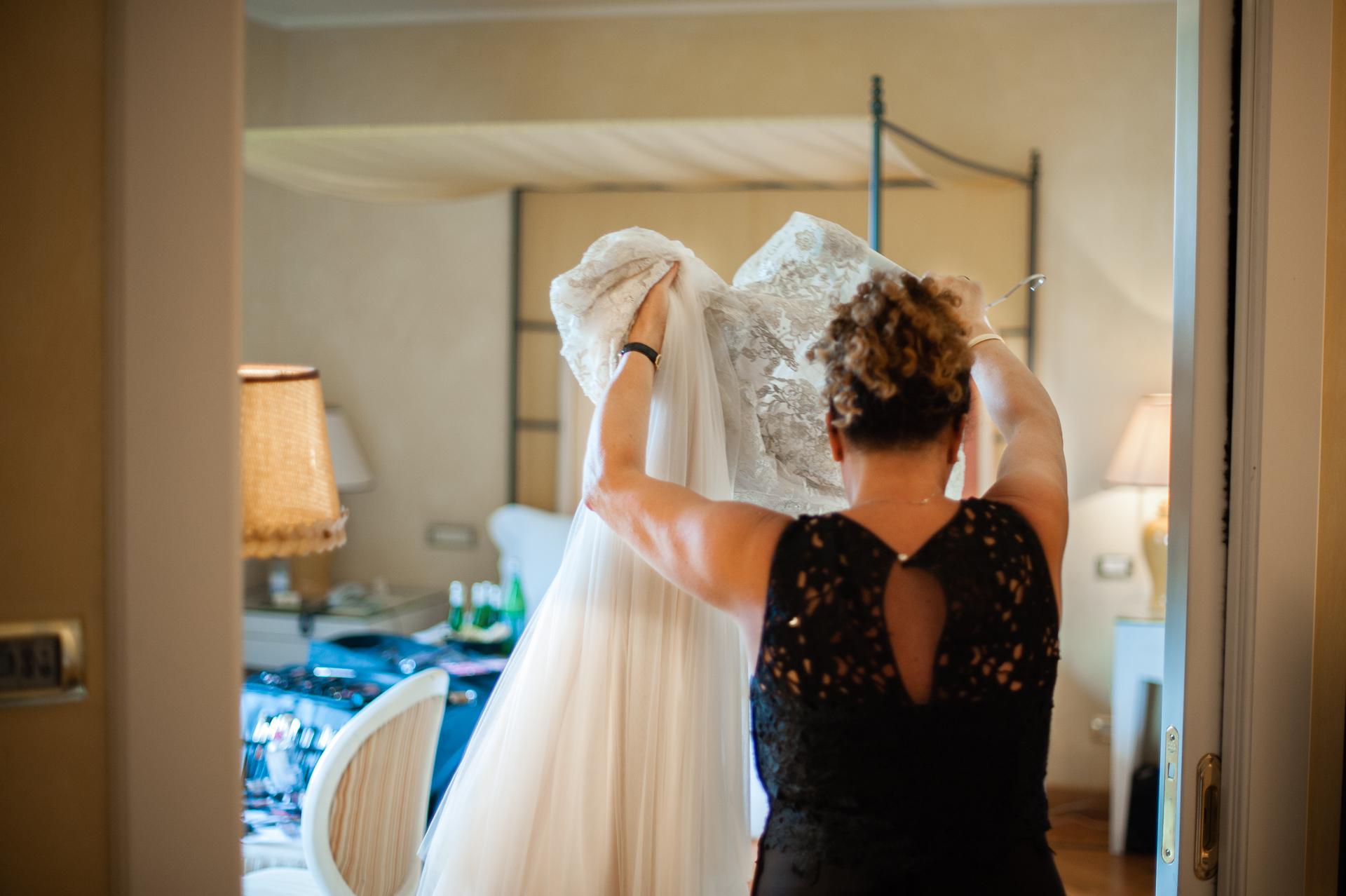 L'Albereta Relais & Châteaux, Erbusco Elopement Bild | Die Mutter der Braut nimmt das Kleid zum Anziehen ihrer Tochter.