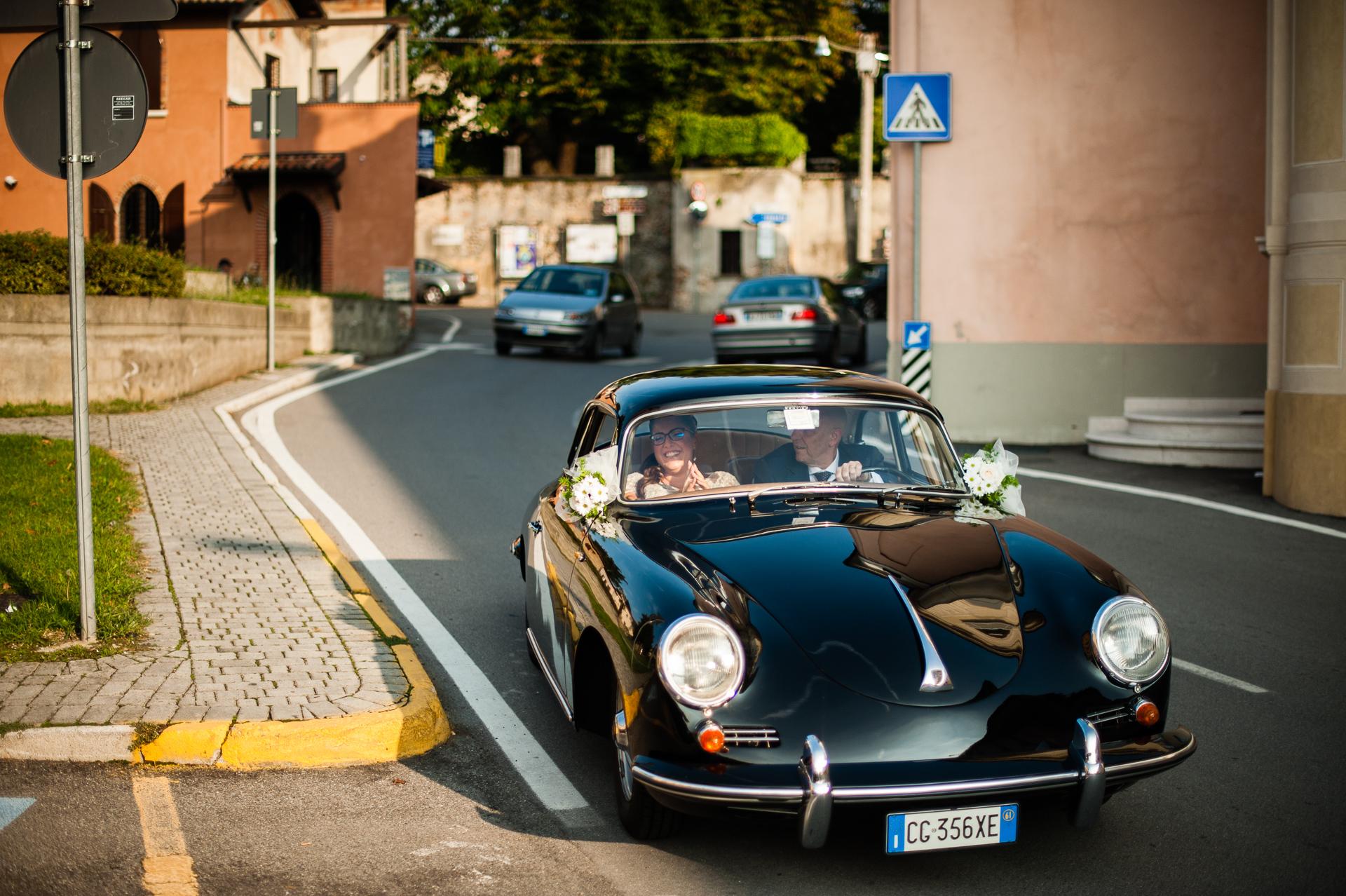 Elopement Bild vom Erbusco Town Hall Elopement (BS) - Die Braut kommt mit ihrem Vater, der ein Jaguar-Oldtimer vom Typ E fährt, im Rathaus an.