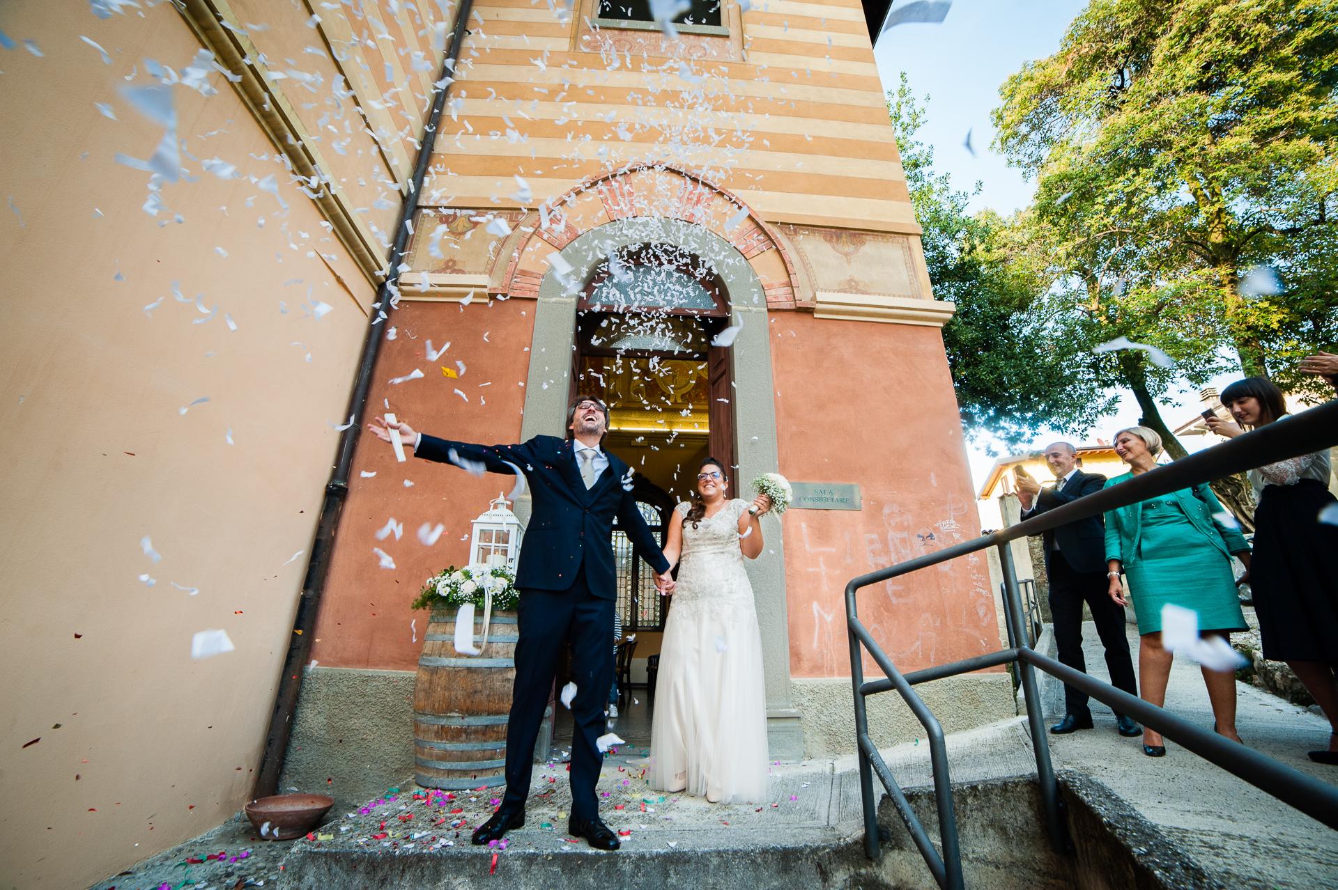 Eloping-Paar nach ihrer Erbusco-Rathauszeremonie - BS | Das Brautpaar verlässt das Rathaus zwischen Konfetti, die über ihm fliegen.