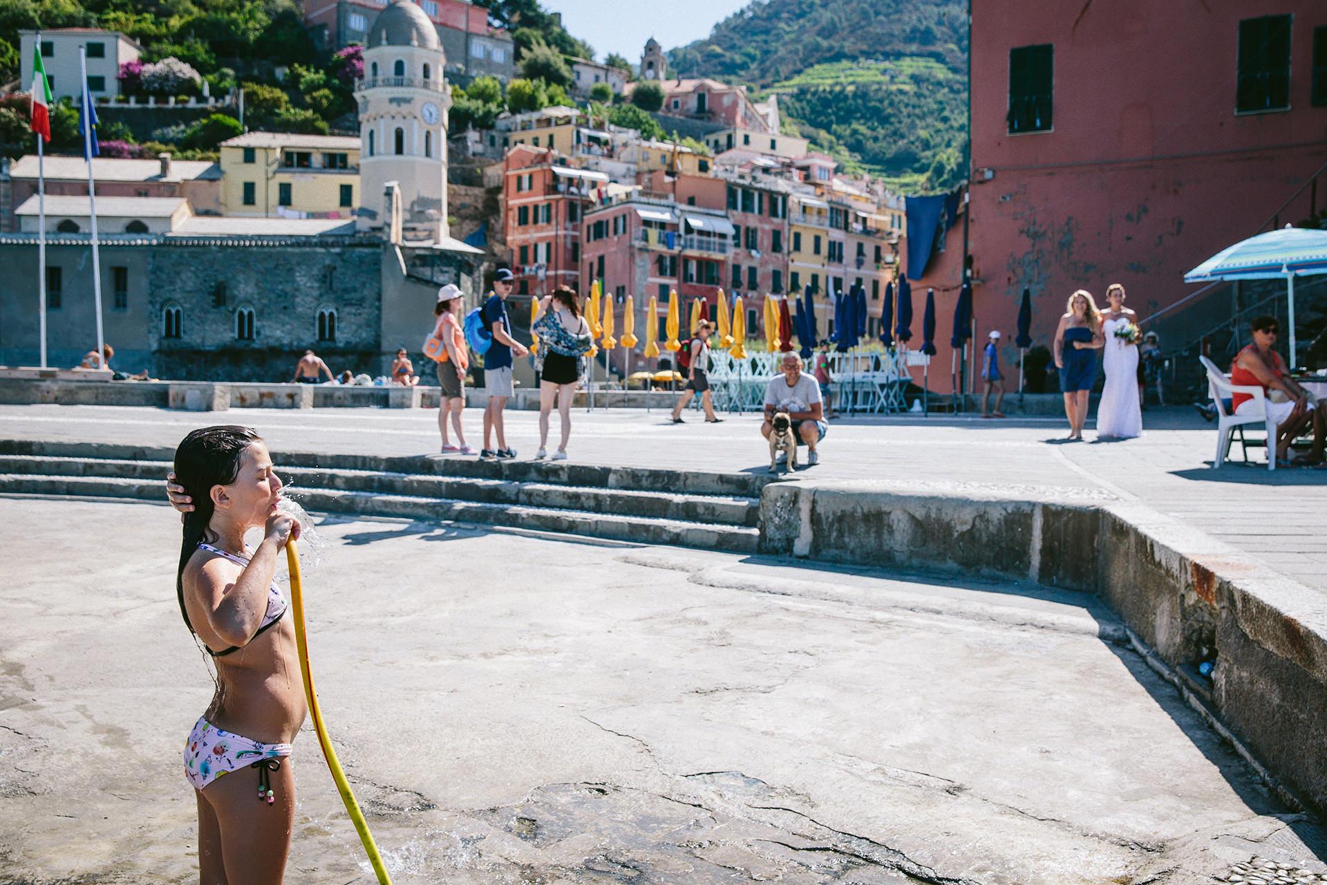 Mariage de village de pêcheurs en Italie - IT Elopement Photo | Mariée et demoiselle d'honneur s'approchant de la jetée de Vernazza