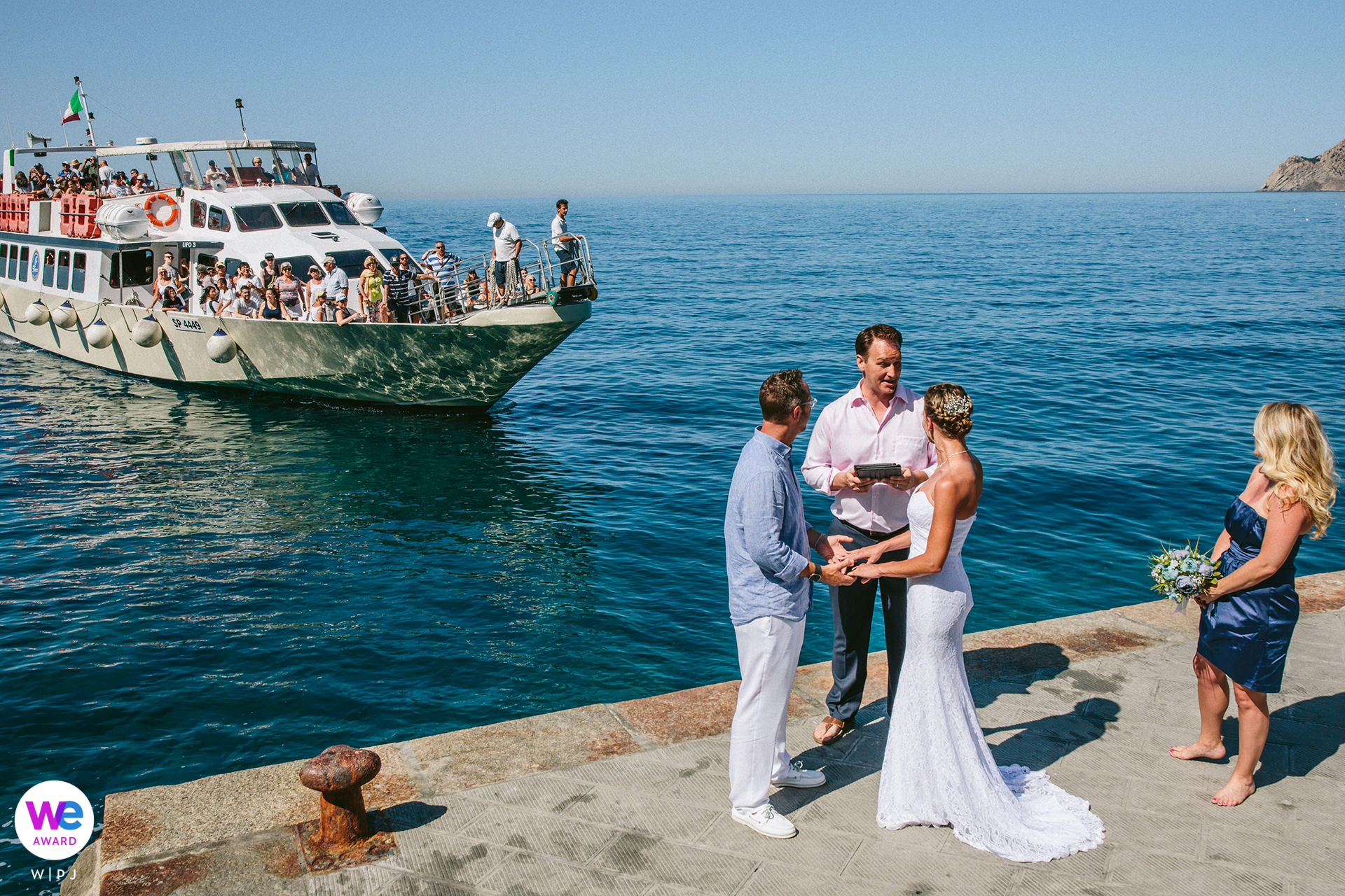 Vernazza, Cinque Terre Italy Elopement Photo from Beach Ceremony | The Cinque Terre ferry making its unplanned and unforeseen entrance in the wedding ceremony. The ferry crowd cheered for the newlyweds.