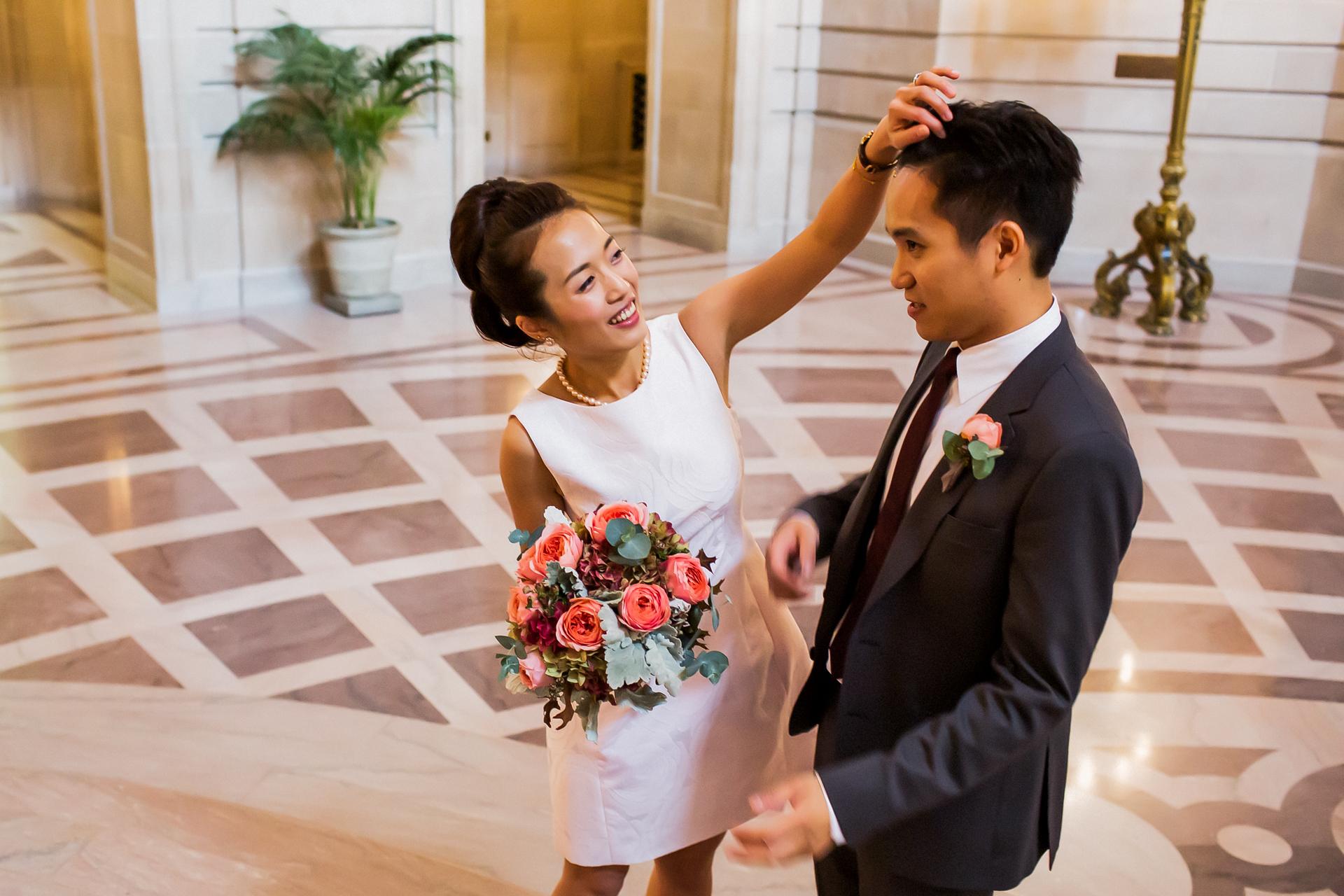 Elopement civil de la boda en el ayuntamiento de San Francisco   La dulce novia se aseguró de que su novio se viera perfecto en esta foto.