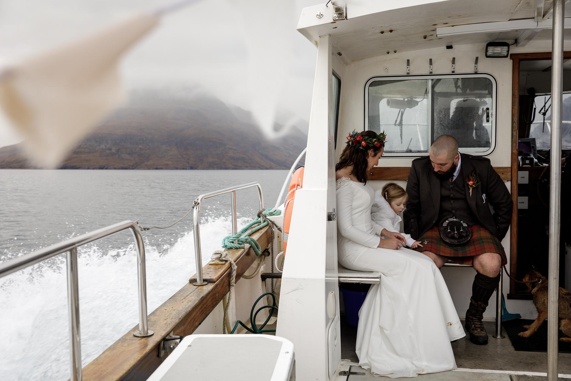 Isle of Skye, Schotland Elopement Image | Het was een beetje winderig tijdens de boottocht van 30 minuten, dus het paar en hun dochter bleven onder dekking totdat we de steiger bereikten waar we van de boot moesten afstappen