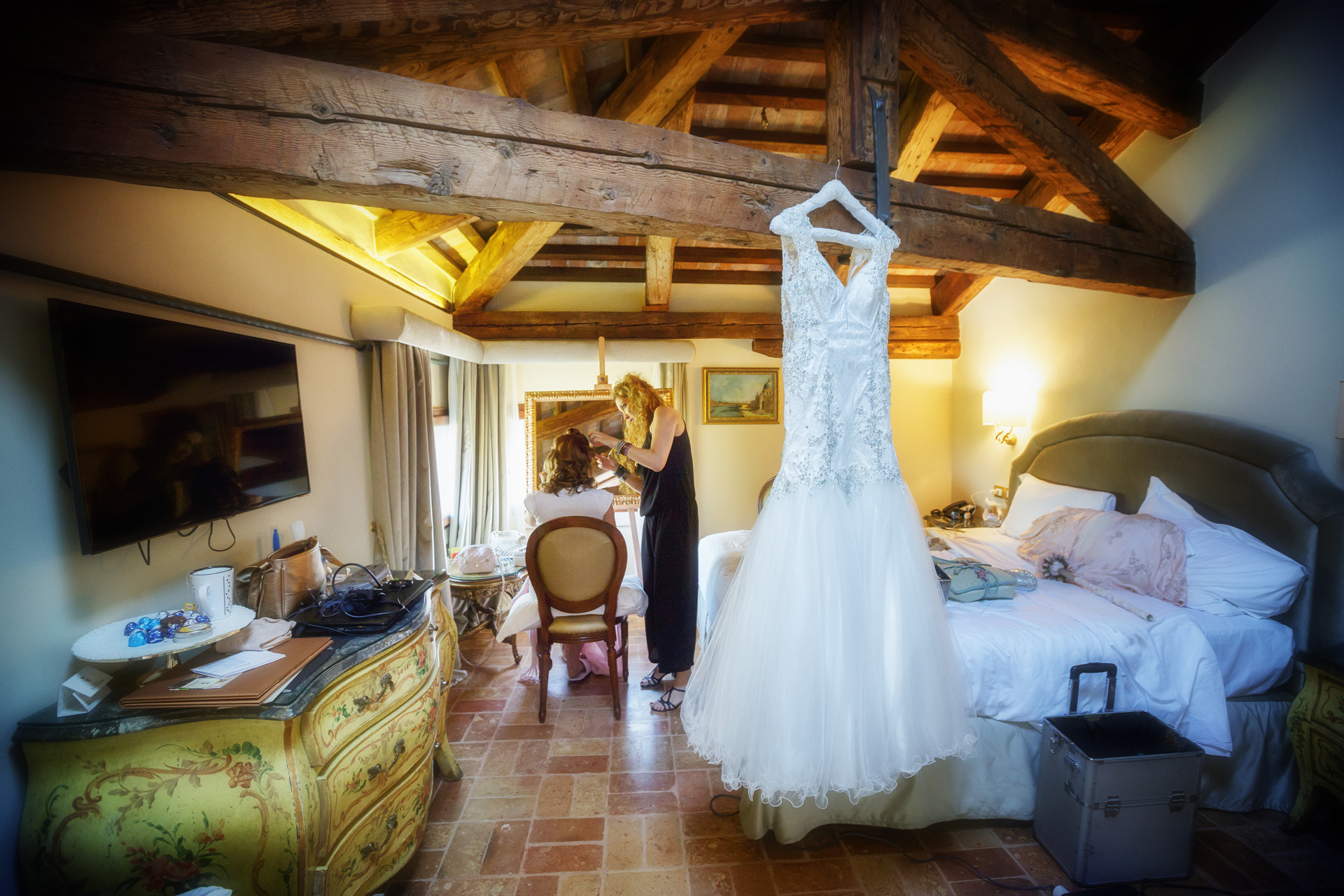 Venecia, Italia Elopement Picture | La novia se prepara mientras cuelga su vestido de novia.