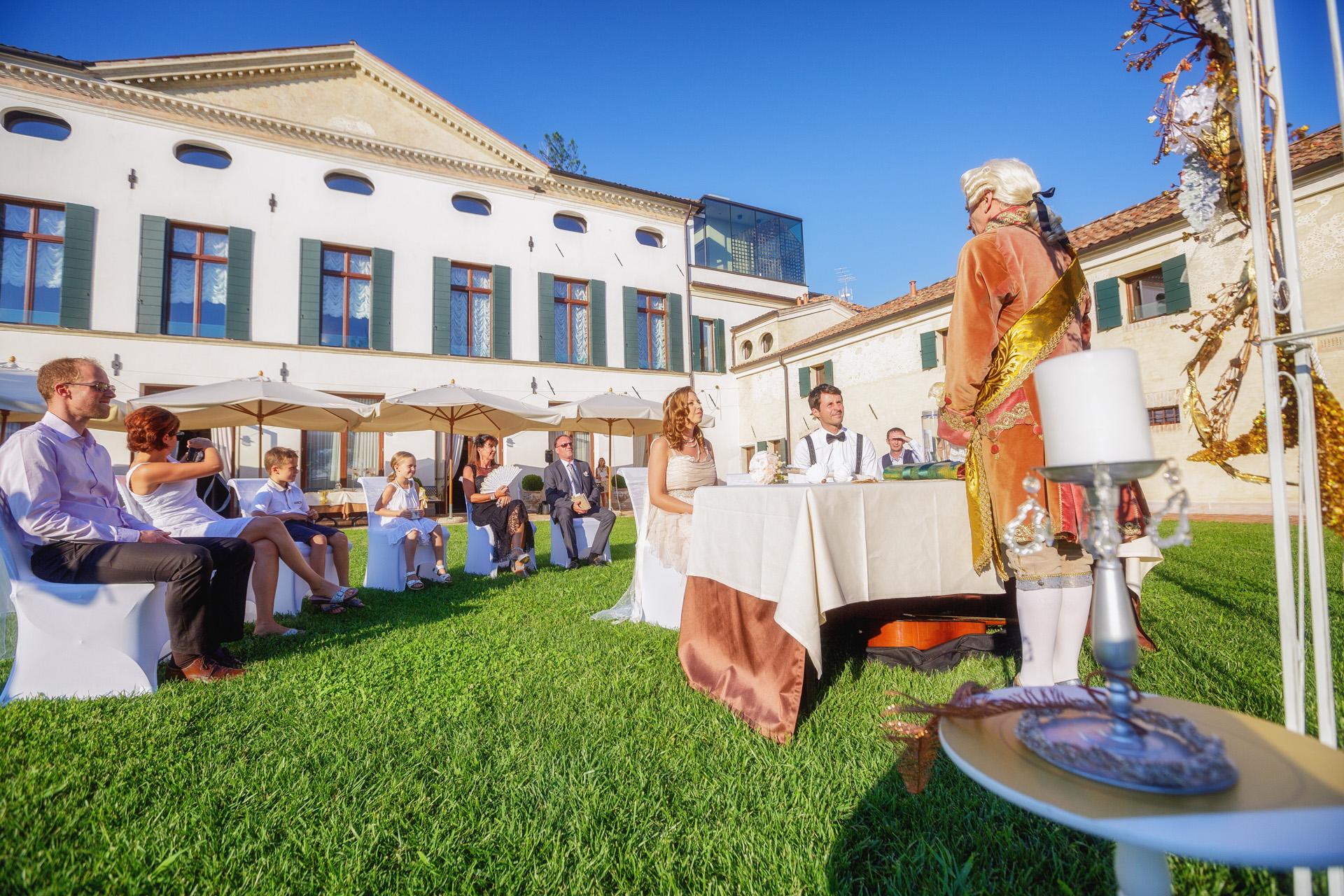 Foto de boda pequeña al aire libre de Venecia, Italia | La simbólica ceremonia de boda al aire libre que incluyó al novio realizando una romántica serenata.