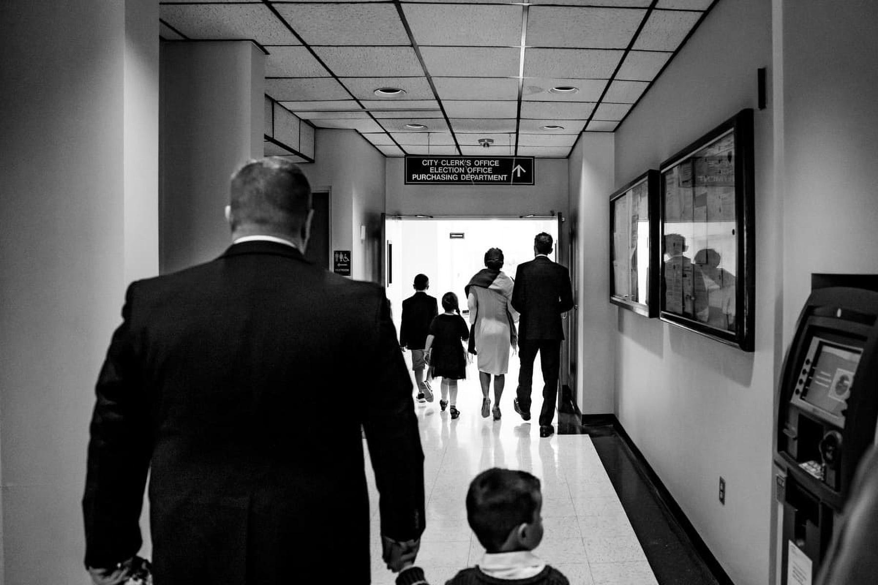 MA City Hall - Foto di matrimoni di piccole dimensioni | la famiglia felice e la coppia di sposi camminano insieme lungo il corridoio, alcuni mano nella mano
