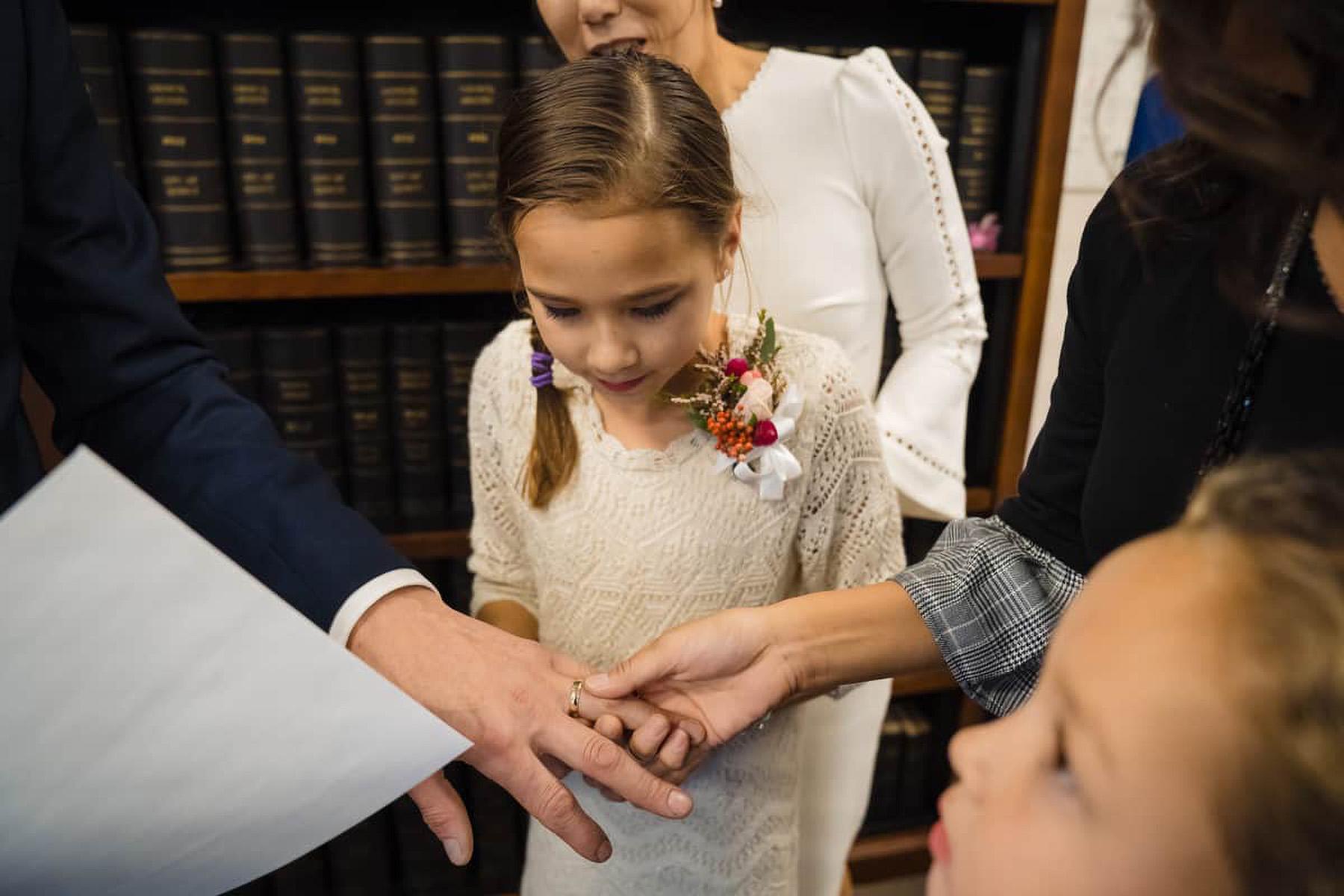 MA - Foto di cerimonia nuziale civile piccola | gli ospiti presenti non vedono l'ora di vedere gli anelli mentre tengono la mano dello sposo per vedere meglio la sua fede nuziale d'oro
