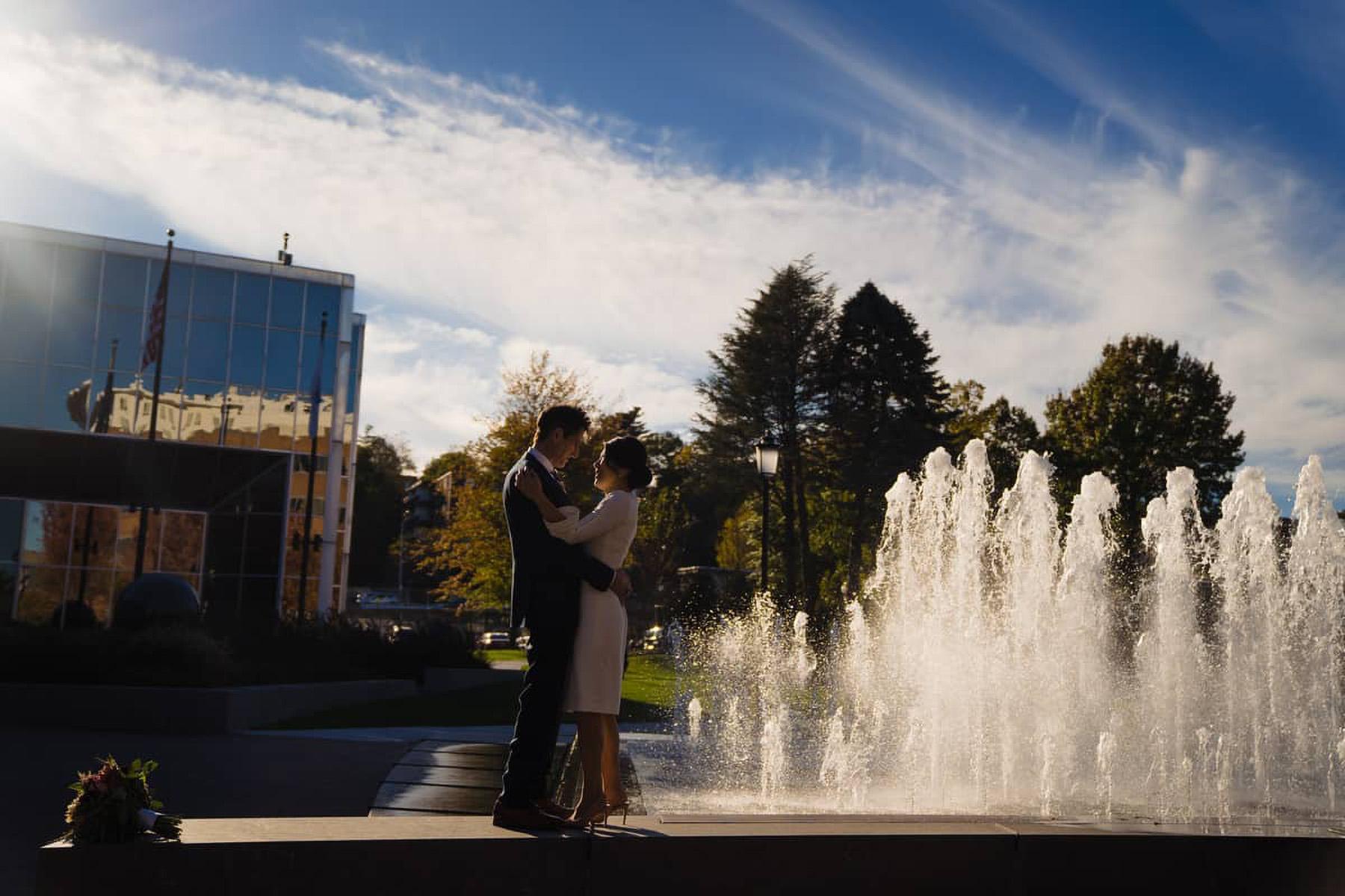 Municipio di Quincy - Foto di matrimoni di piccole dimensioni | gli sposi stanno accanto a una grande fontana e condividono il momento insieme, guardandosi negli occhi
