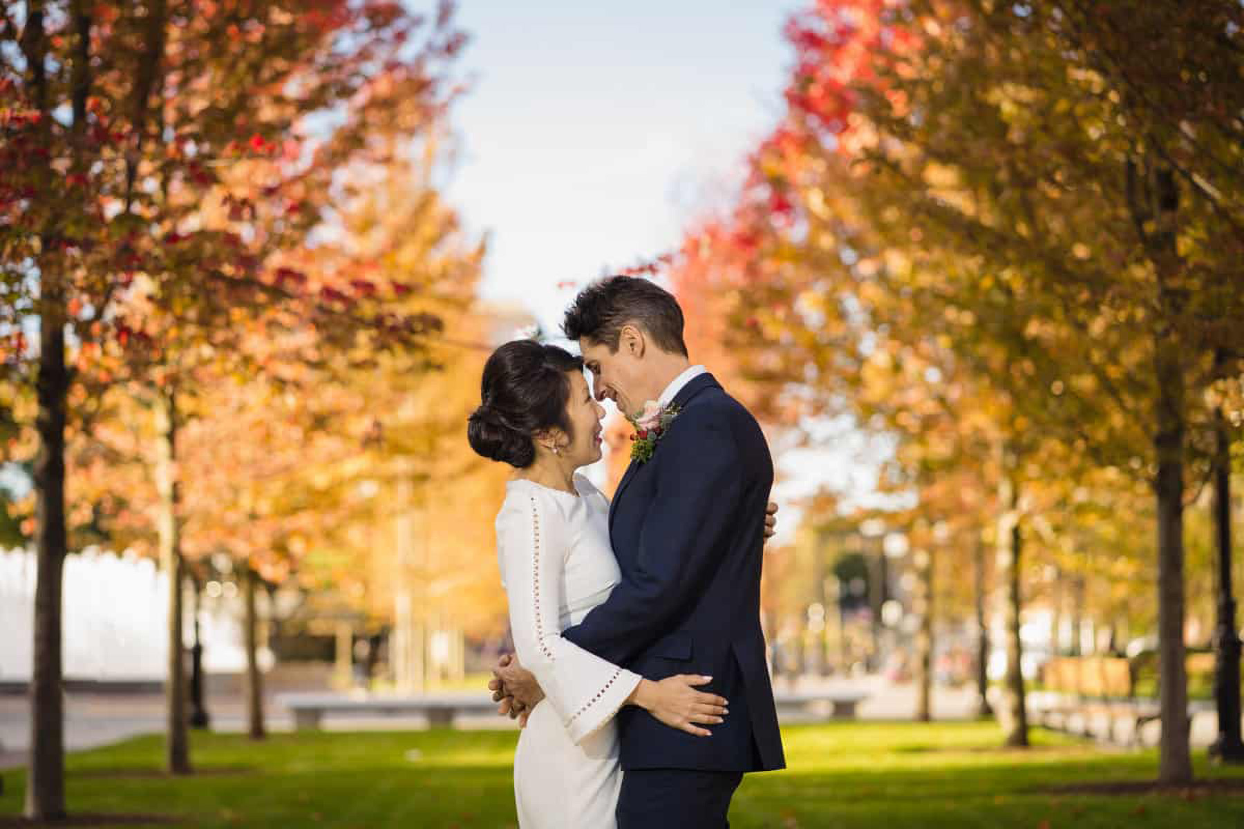 Quincy, MA Town Hall - Ritratto di matrimonio piccolo elastico | la coppia coglie l'occasione per tenersi l'un l'altro fuori tra una fila di alberi con foglie colorate