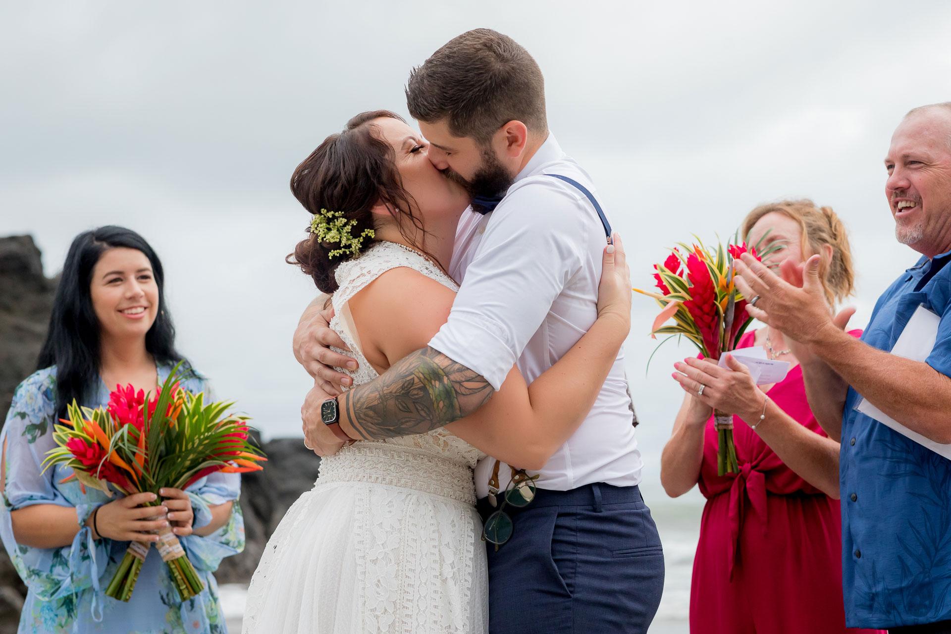 Cérémonie de la plage du Costa Rica Elopement Kiss Image   Premier baiser entouré de sa famille