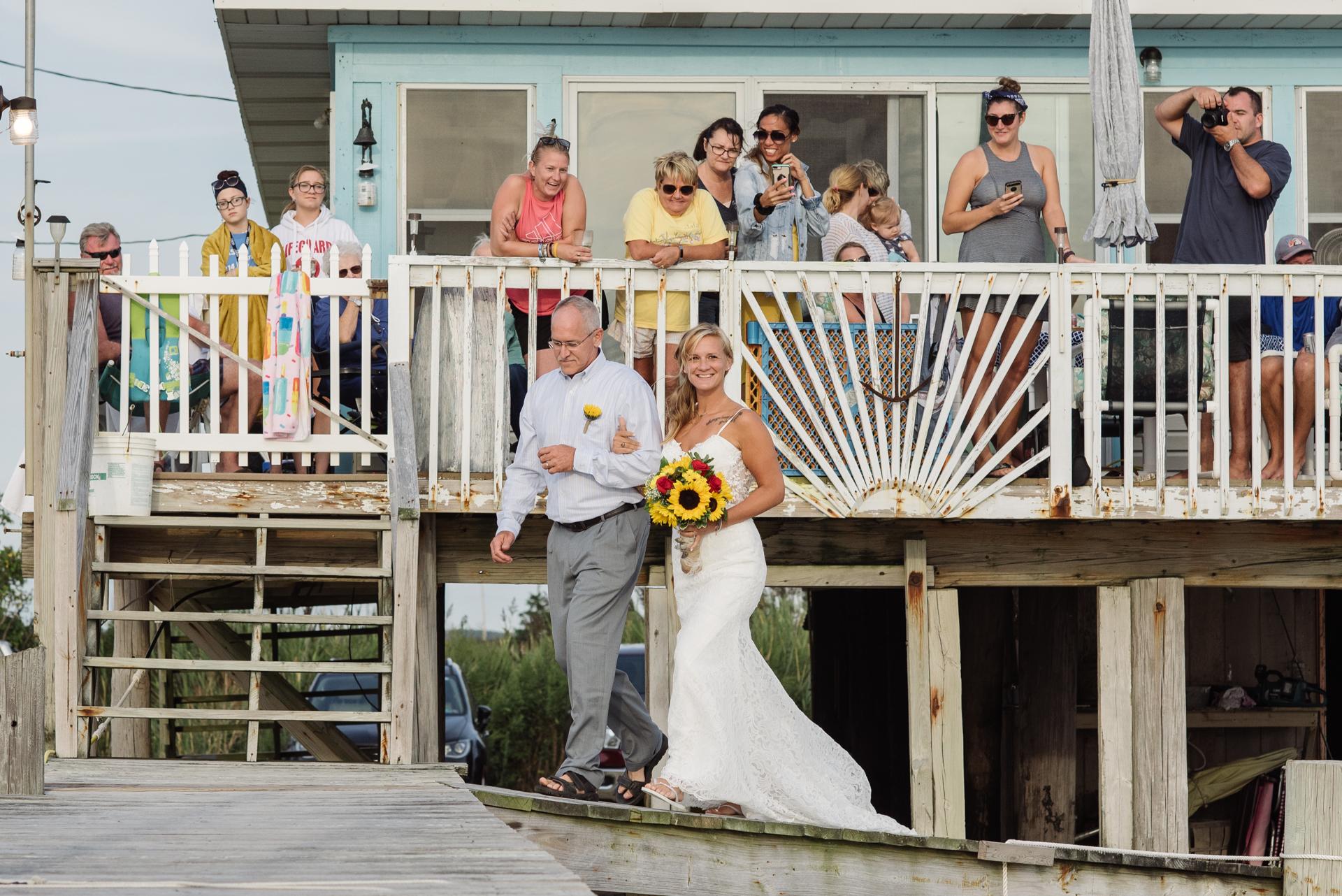 Sea Breeze, New Jersey Outdoor Elopement Fotos | Der Vater der Braut führt seine Tochter an erweiterten Familienmitgliedern vorbei und auf das Dock, auf dem die Hochzeitszeremonie stattfand