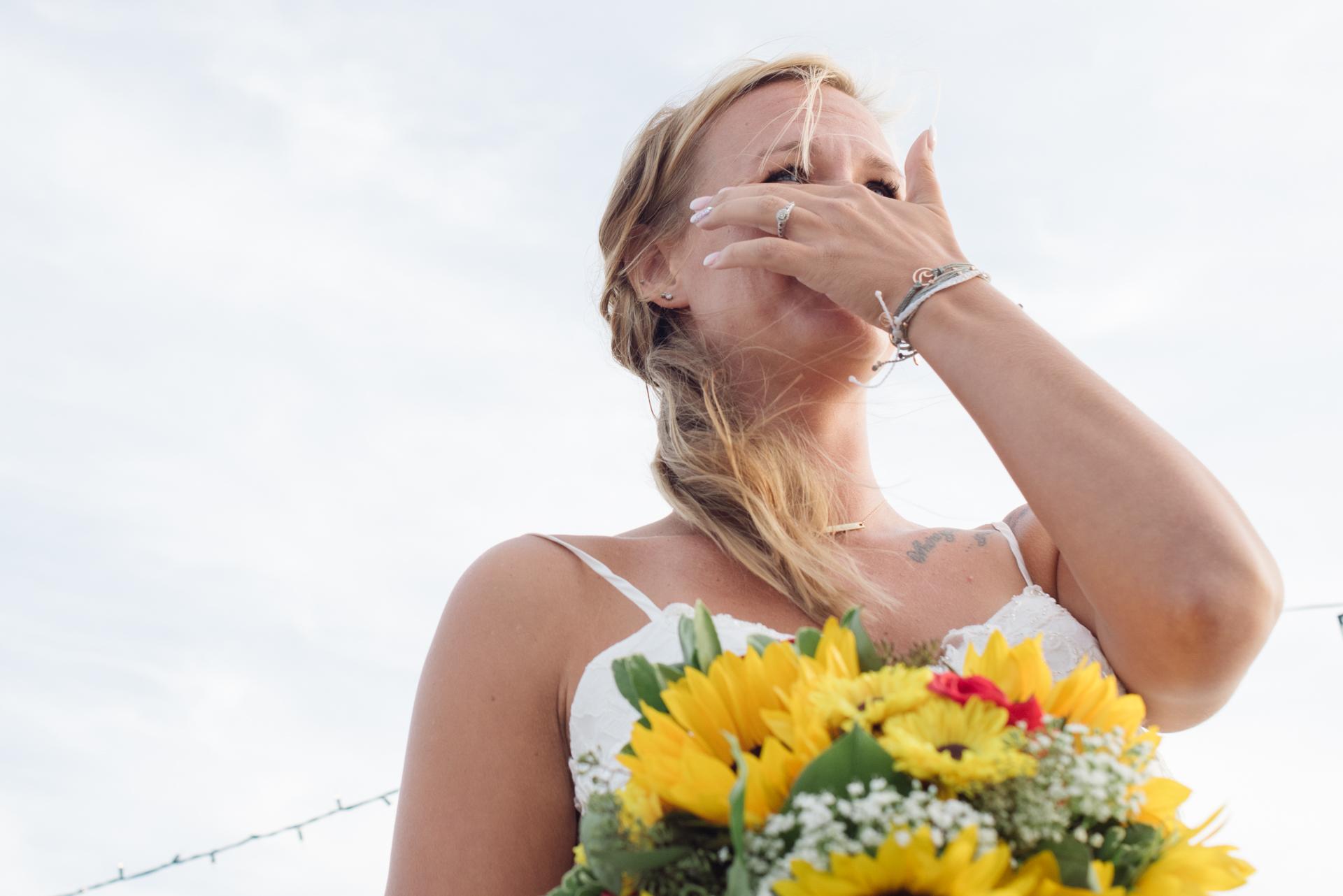 Sea Breeze, New Jersey Beach Elopement Fotos | Die Braut wischt sich die Tränen ab, während sie während ihrer Hochzeitszeremonie emotional wird