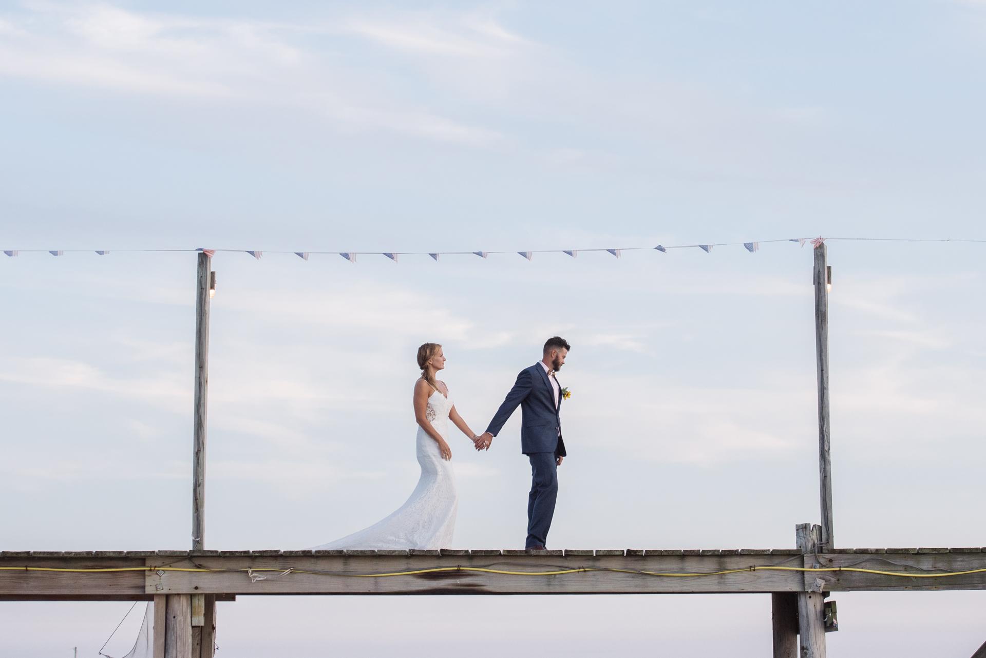Meeresbrise, New Jersey Beach Elopement Porträt | Ein Porträt der Braut und des Bräutigams, die entlang des Docks gehen, wo ihre Hochzeitszeremonie stattfand