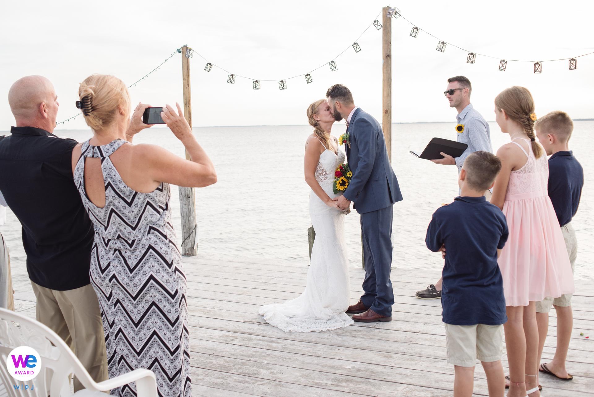 Sea Breeze, New Jersey Elopement Zeremonie Bild | Braut und Bräutigam teilen einen ersten Kuss vor ihren engsten Familienmitgliedern