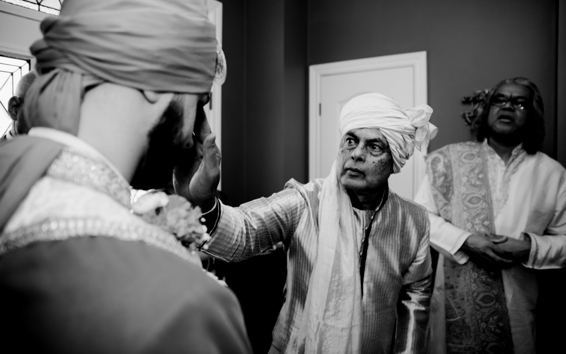 Coronavirus (COVID-19) Toronto Elopement Picture | The father of the bride is welcoming the groom and his family by applying red powder (KUMKUM) on his forehead