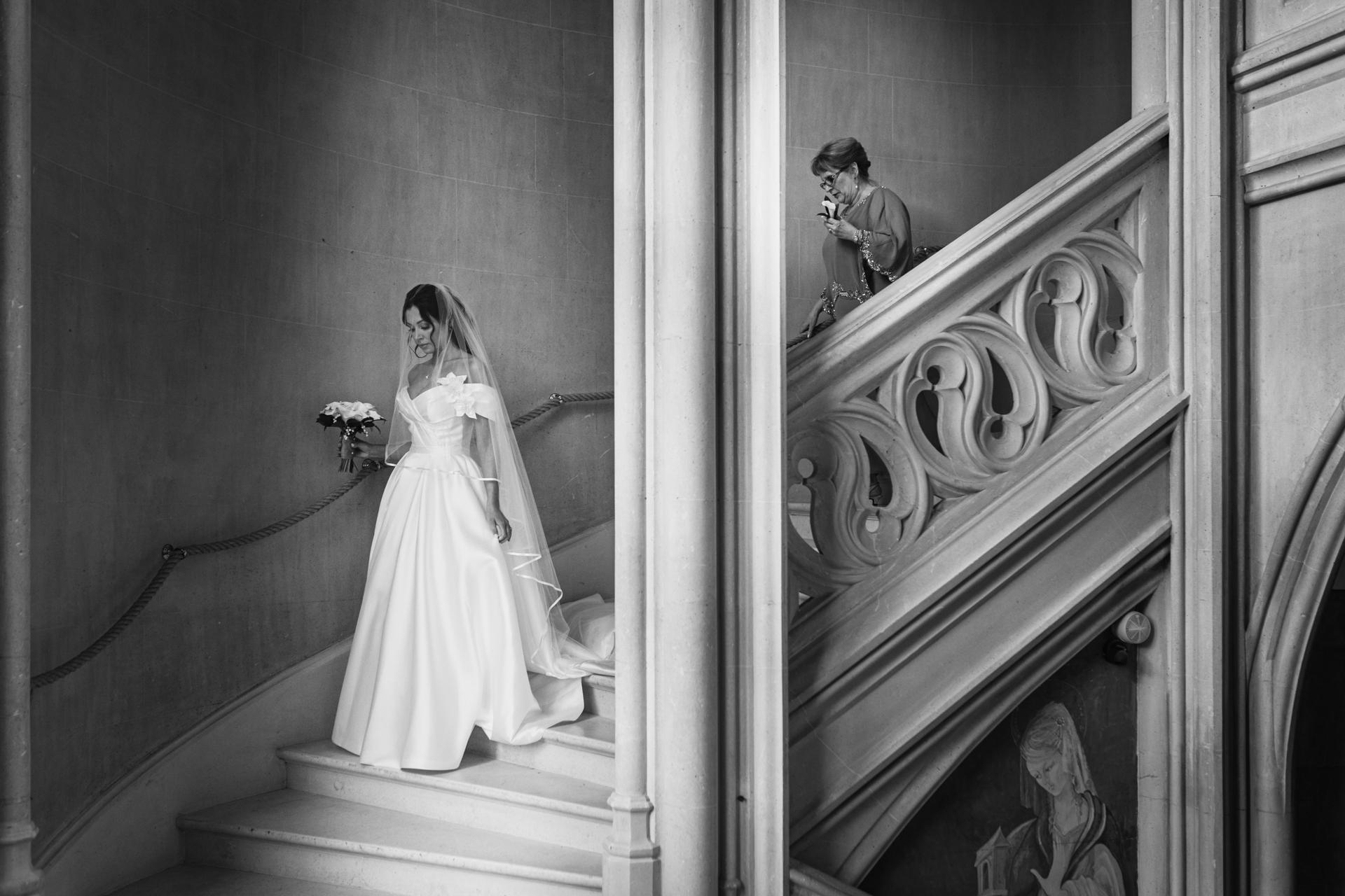 Frankreich Elopement Bild | Die Braut geht in ihrem Hochzeitskleid eine schöne Steintreppe hinunter, während sie ihren Blumenstrauß in einer Hand hält