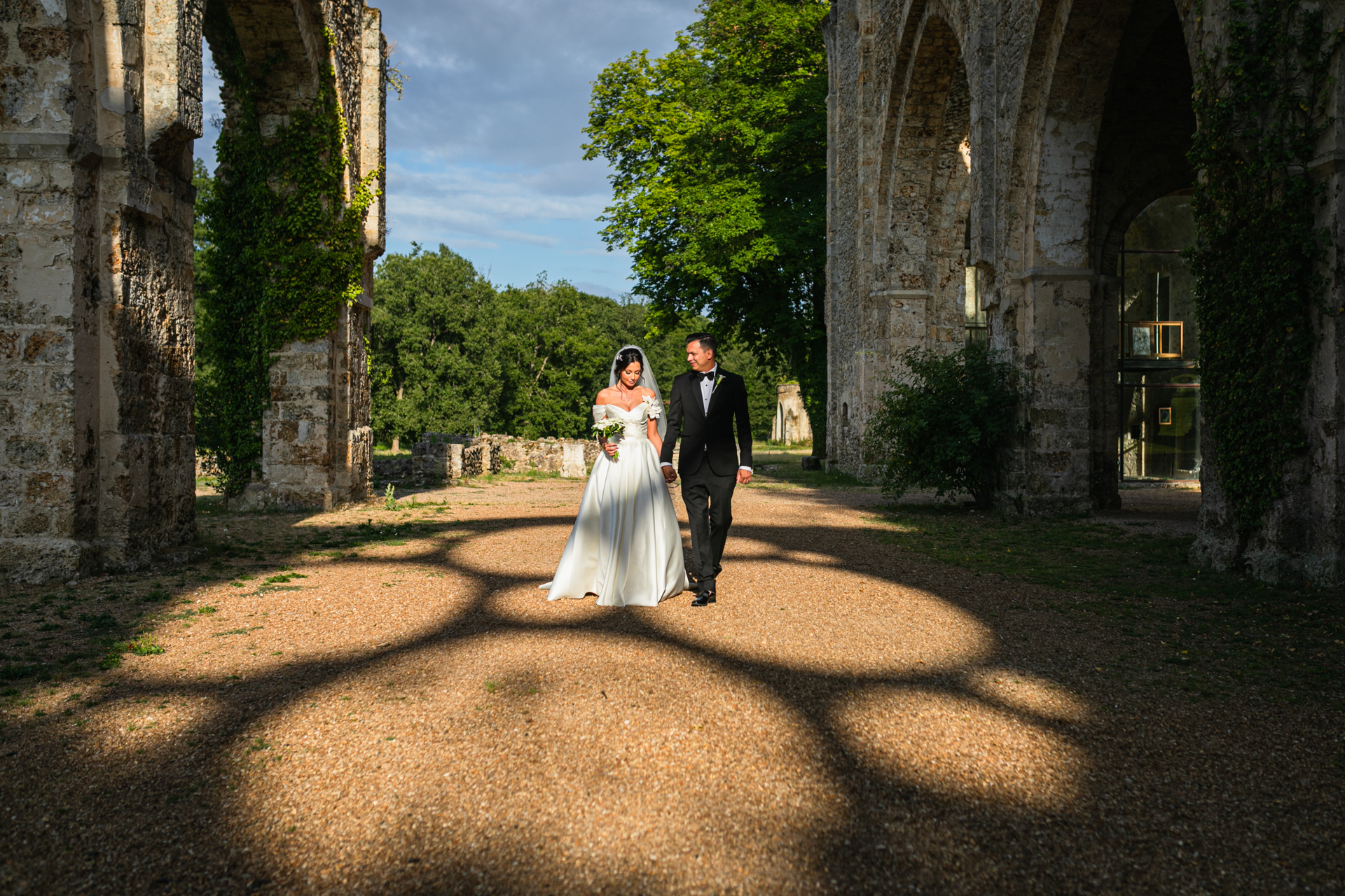 France Abbey Elopement Picture | The newlywed couple walks hand-in-hand through archways.