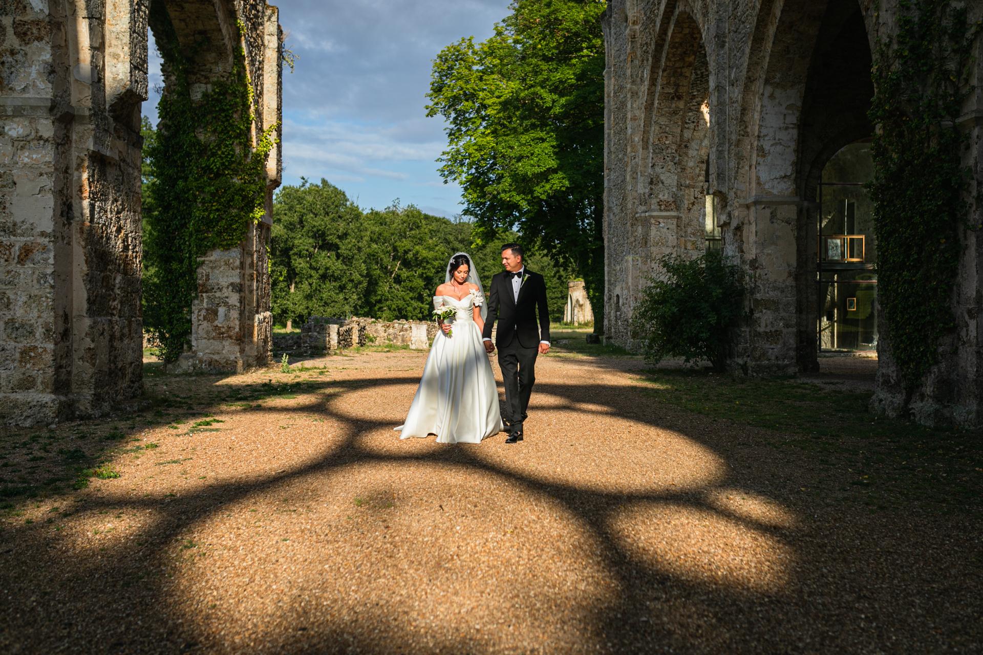 Frankreich Abbey Elopement Bild | Das frisch verheiratete Paar geht Hand in Hand durch Torbögen.