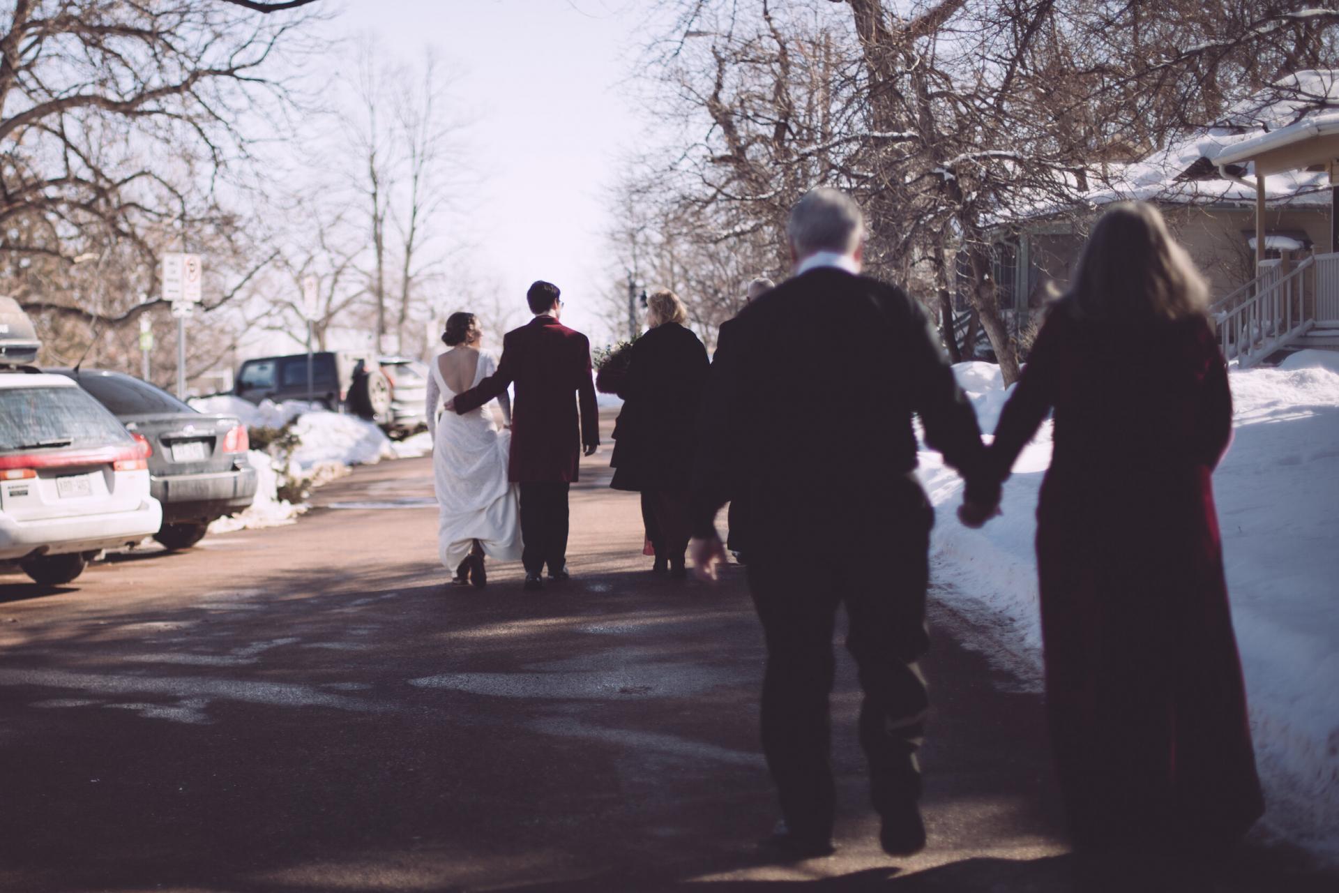 Colorado Winter Elopement Bild | Die Gruppe geht die Straße entlang in Richtung eines Restaurants, um zu feiern. Das Brautpaar geht voran