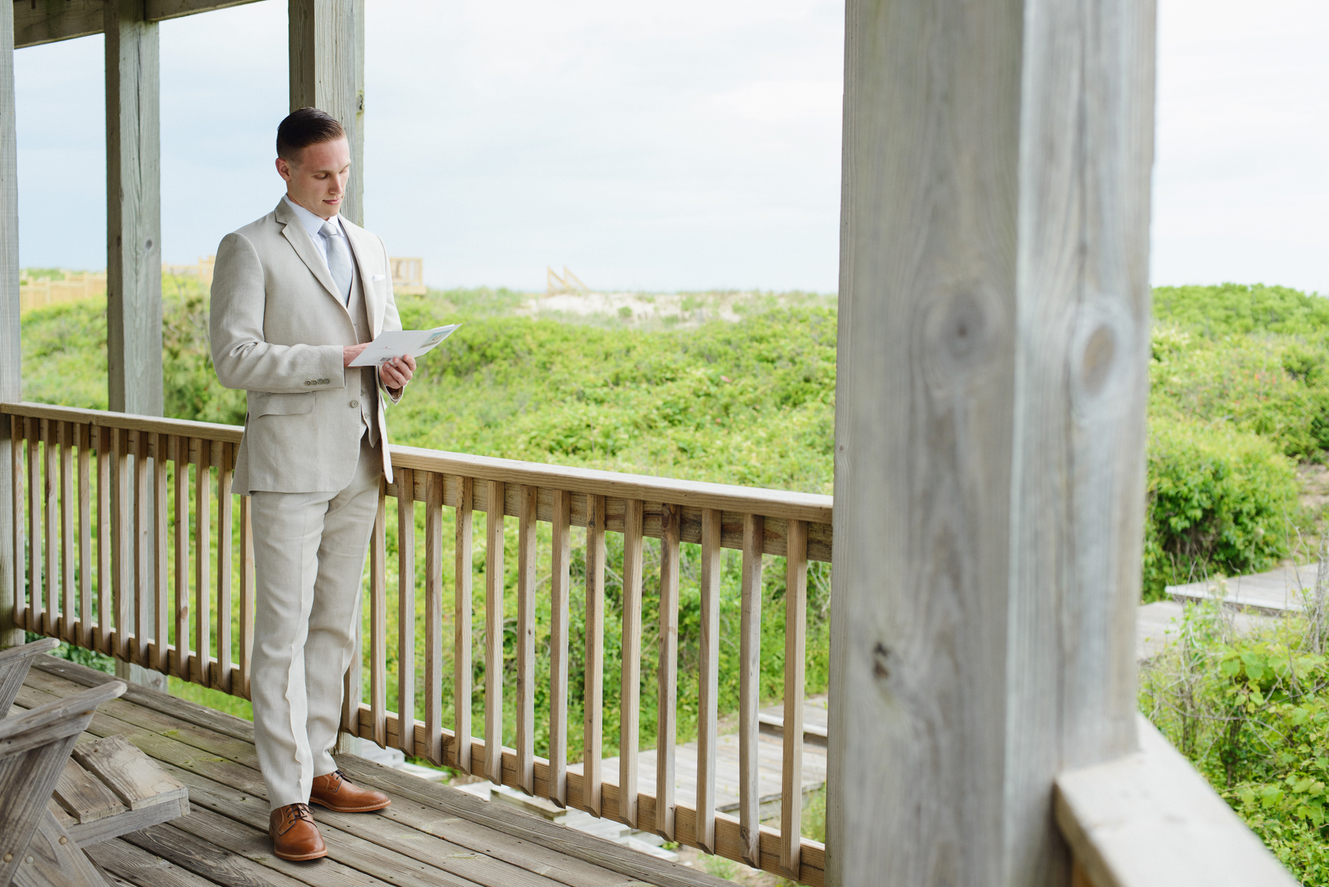 Corolla, North Carolina Elopement Getting Ready Image | Groom reading letter from the bride before their wedding ceremony