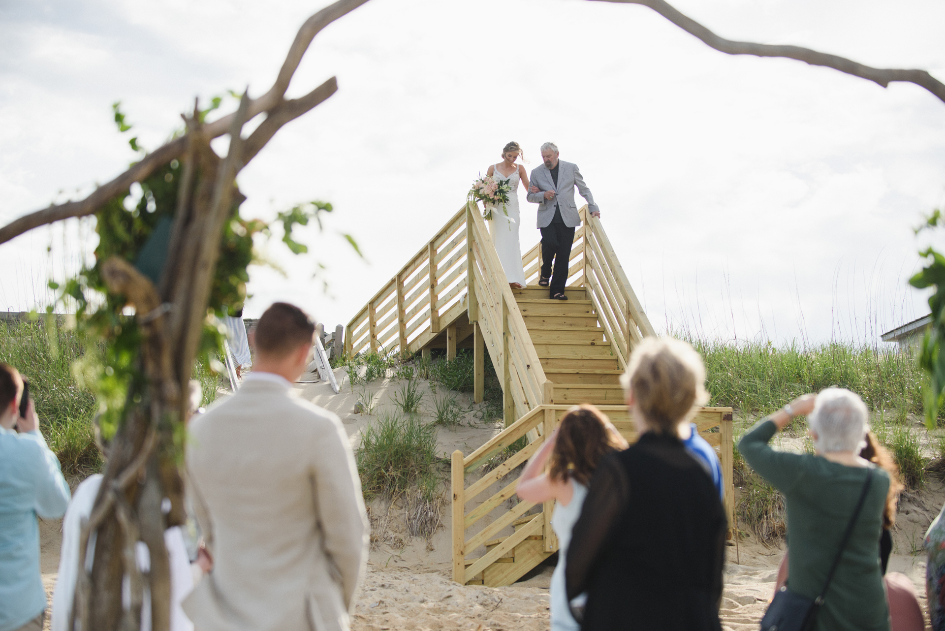 North Carolina Beach Elopement Ceremony Image | The bride and her father walk down beach stairs to the wedding ceremony