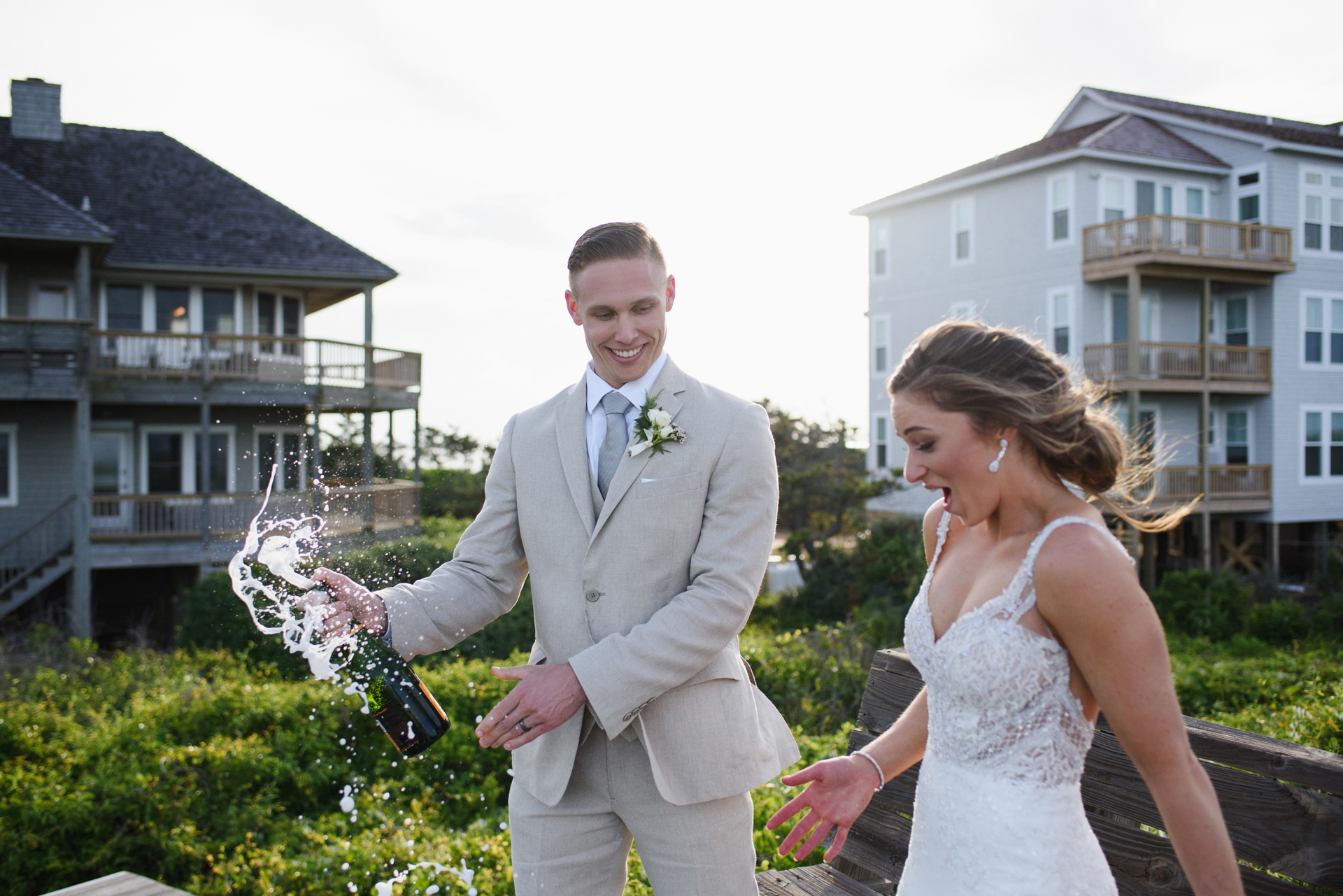 North Carolina Small Wedding Ceremony Photo | The bride and groom are sprayed with champagne while opening a bottle together
