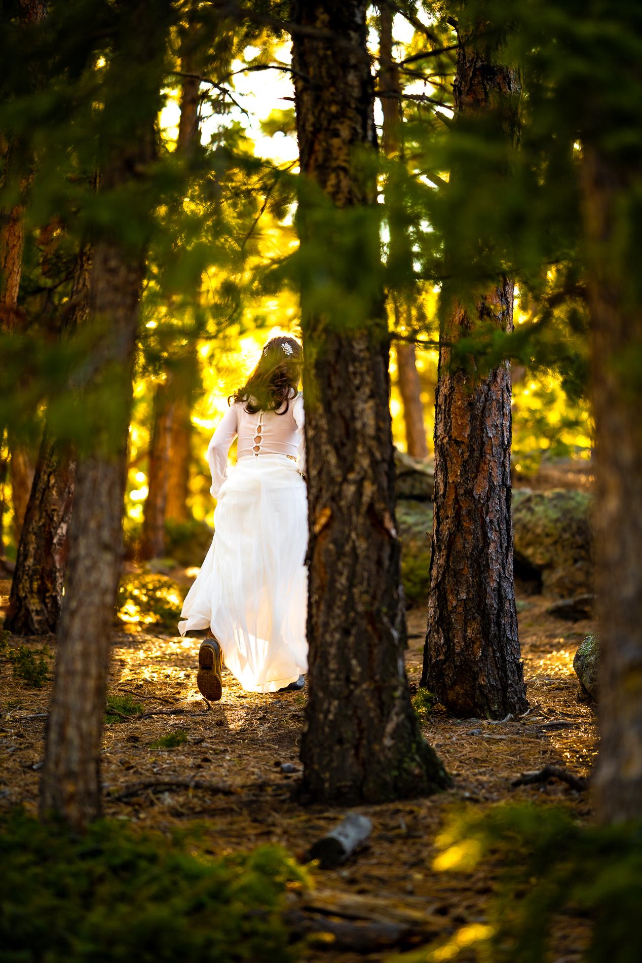 Colorado Elopement Photo | La mariée ouvre la voie en s'aventurant dans les bois, à la recherche du meilleur endroit pour échanger leurs vœux