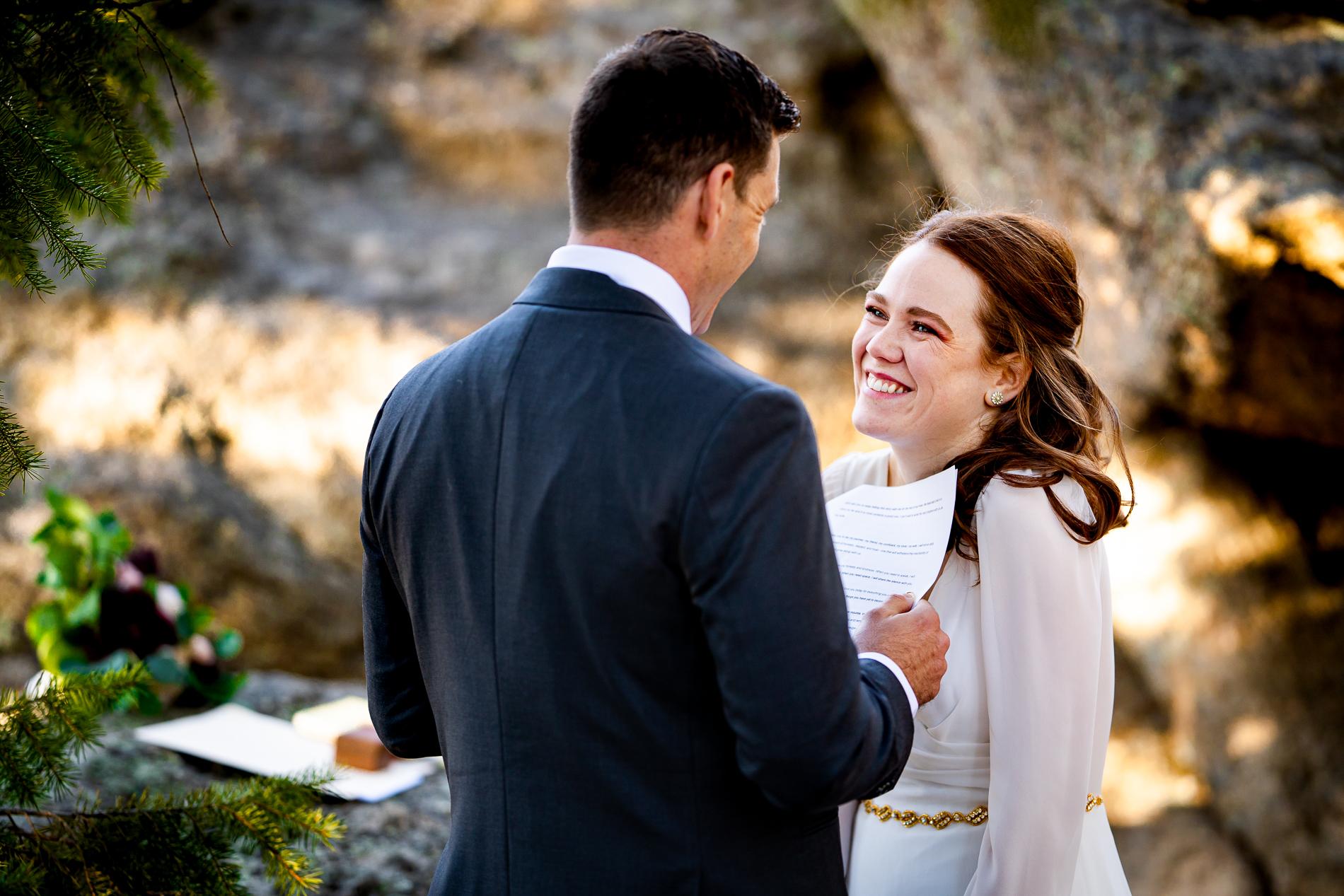 Colorado Elopement Ceremony Photographie | La mariée rit tandis que le marié lui lit ses vœux lors de leur cérémonie privée