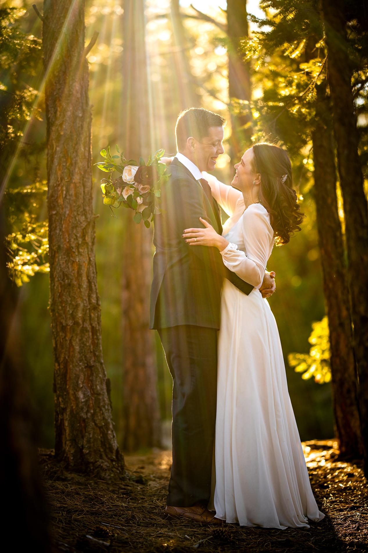 Photographie de mariage Colorado Elopement | La mariée et le marié posent pour un portrait dans les bois alors qu'une belle lumière dorée brille à travers les arbres