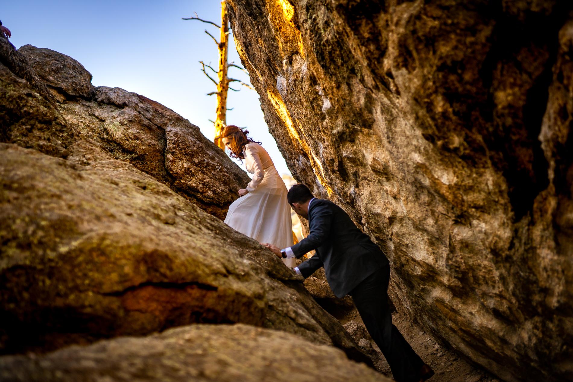 Photo de mariage Colorado Elopement | La mariée et le marié escaladent un terrain rocheux après leur fuite privée