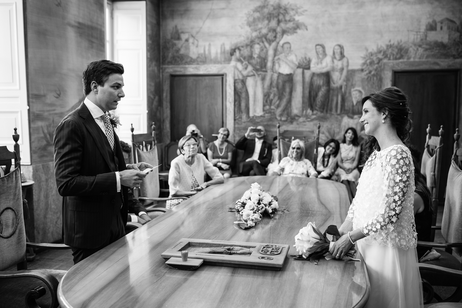 Lugano Town Hall, Switzerland Elopement Wedding Ceremony Photo | The bride and groom both stand while the groom reads his vows to the bride across the table. She can't help but smile, nor can the guests sitting around the table