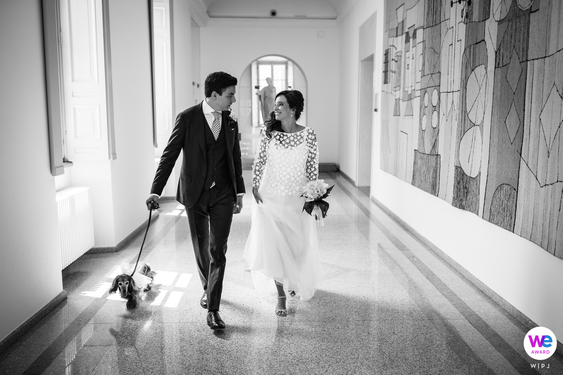 Lugano Town Hall, Switzerland Elopement Photo Story | The bride and groom make their way to the hall where the ceremony will be held with their dog walking ahead of them eagerly across the shining tile floor